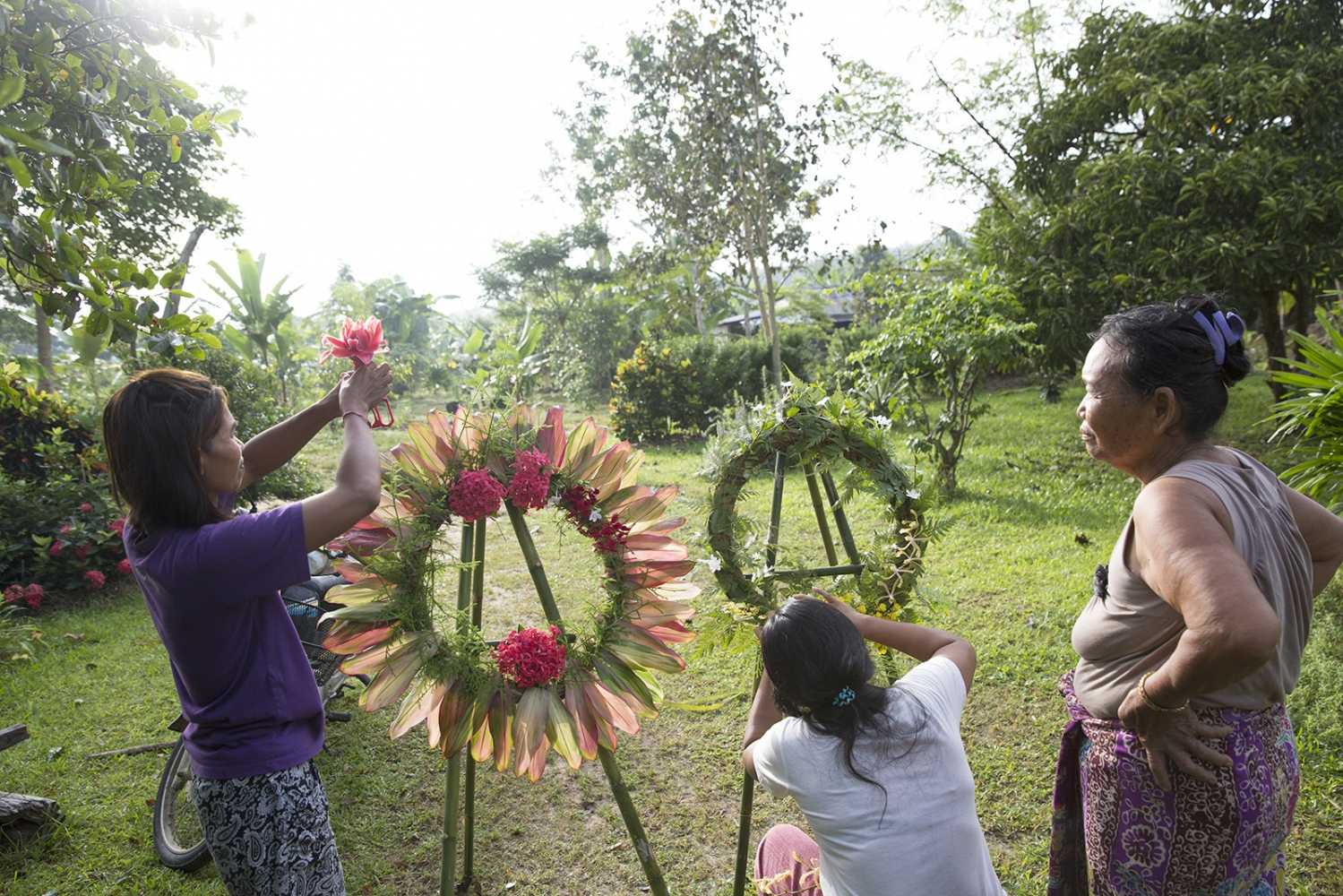 Women make reefs out of leaves and flowers as part of the memorial day of Klong Sai Pattana village in remembrance for each of the four people murdered during their prolonged fight to remain on the land. December 2016.