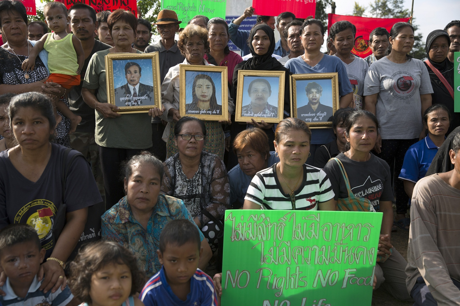 Members of Klong Sai Pattana community, as well as members of other villages in a similar situation, gather for a group photograph during their annual memorial day. Events such as this help the communities cope with their situations by eliminating the feeling that they are not alone in the struggle. They hold pictures of the 4 people killed during their prolonged struggle against a palm oil company. The framed photo seen in the photograph shows the first victim called Somporn Pattaphum who was shot dead on 11 January 2010 a few hundred meters away from where they now sit. December 2016.