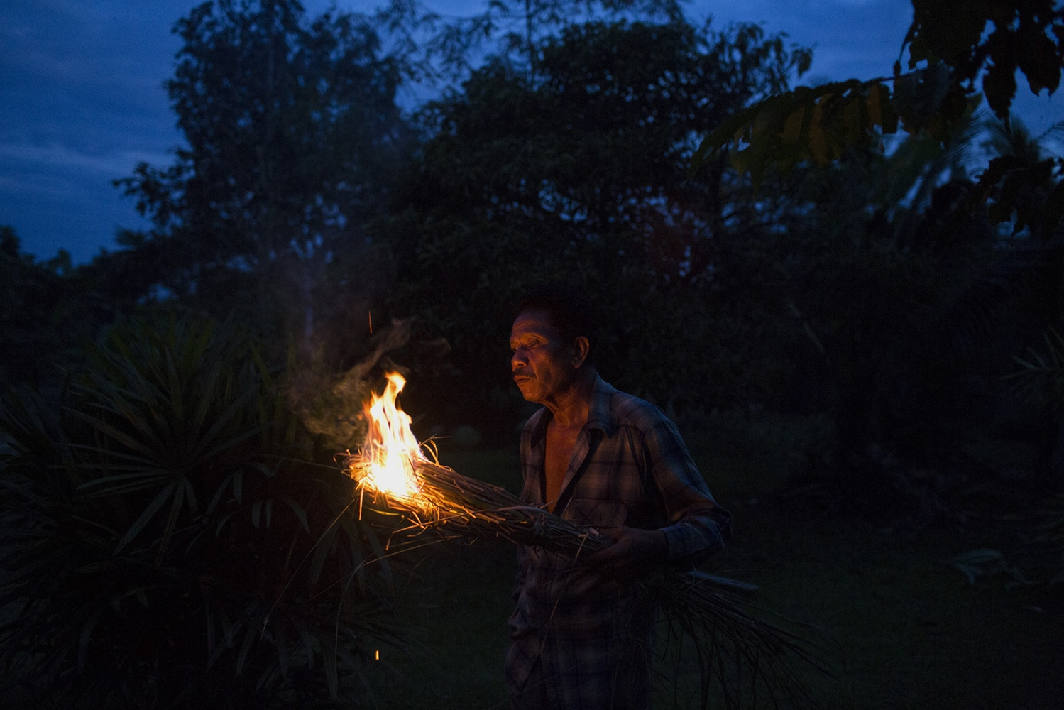 Pratip Rakhungthong, 61, lights dried lemongrass grown in the village to keep away mosquito's. December 2016.