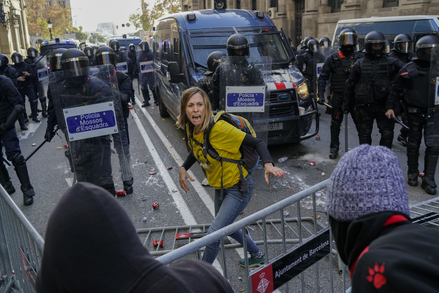 A peaceful protester tries to stop fellow protesters from breaching a police barrier and disrupting the Spanish Cabinet from holding a meeting in Barcelona, Dec. 21, 2018.