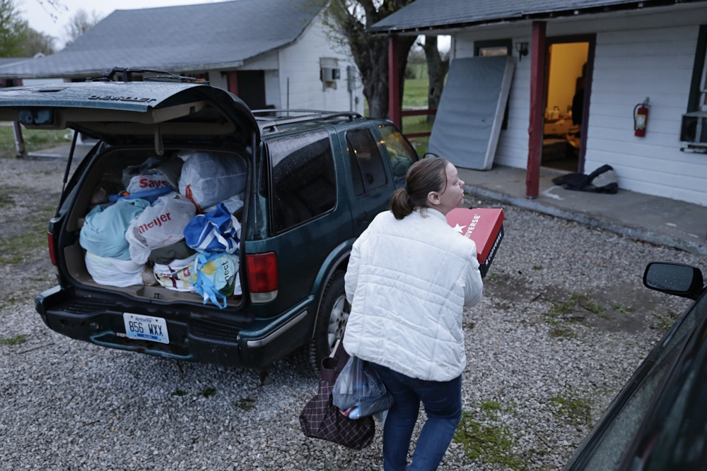 Laurie Brown takes some of her things into Park Cozy Apartments in Cave City, Ky., an extended-stay motel.
