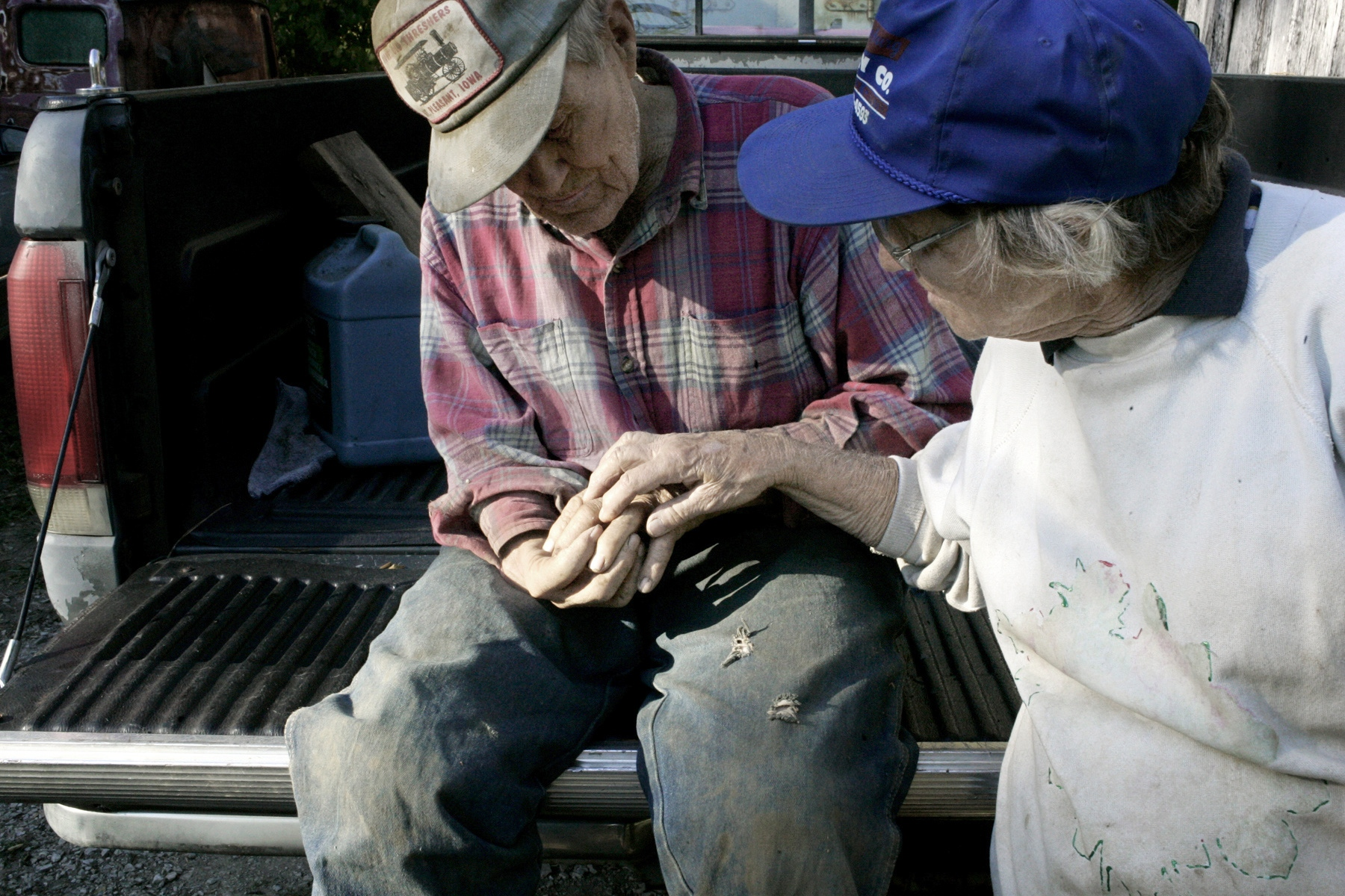 Louise Buntain inspects the hand of her husband Bert. Bert injured his hand while welding on his truck.