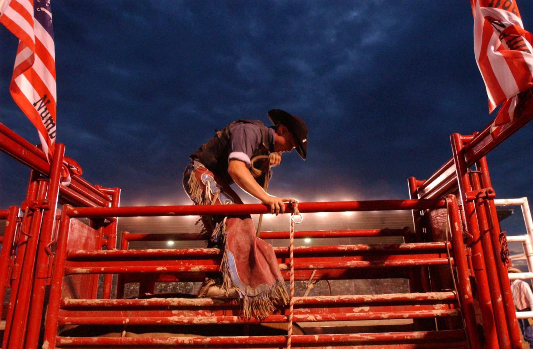 Lowell, Mich. resident Brad Russ helps a friend prepare for the bull riding event during the Flying Star Rodeo held at the Monroe, Mich. fairgrounds.