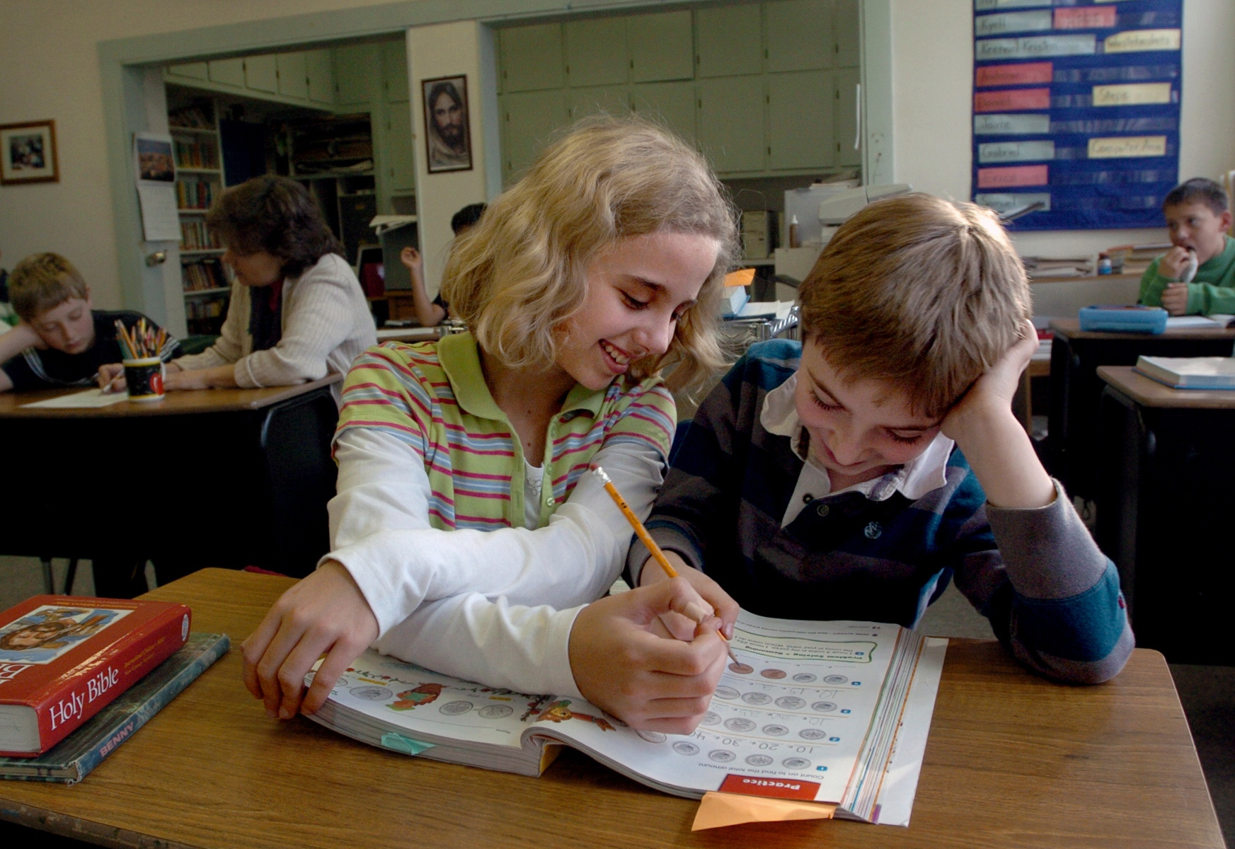"Jaime Hunt, 11, left, helps her classmate Kyell Crary, 8, right, at Estabrook School in West Lebanon, N.H. Estabrook operates as a ""one-room"" schoolhouse and is part of the Seventh-day Adventist Church. Along with lessons in reading, writing and math, students are taught scripture and guided in prayer."
