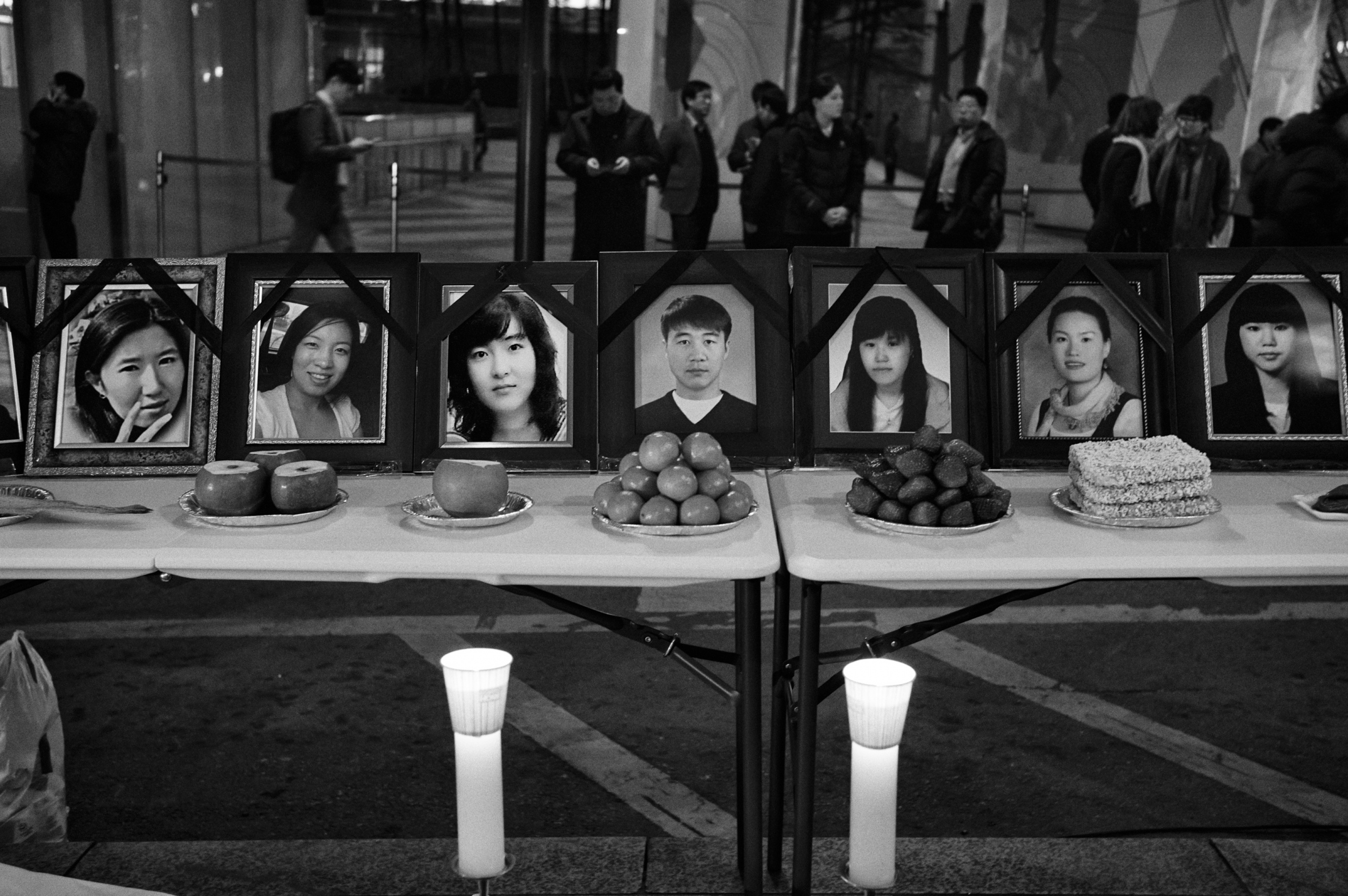 "Portraits of the deceased factory workers of Samsung Electronics and foods are set on the table for the memorial of the victims in front of Samsung Town Headquarters in Seoul, South Korea on Mar. 6, 2013. The victims' families and ""Banolim,"" an activist group which supports and helps the victims hold the memorial ritual for the victims on every March 6th since 2008. The victims who worked in Samsung Electronics semiconductor chip and display factories died of critical disease like leukemia, cancer and brain tumor due to toxic chemicals they had handled during manufacturing processes. According to Banolim, 112 former semiconductor chip and display factory workers have died among 306 reported cases."