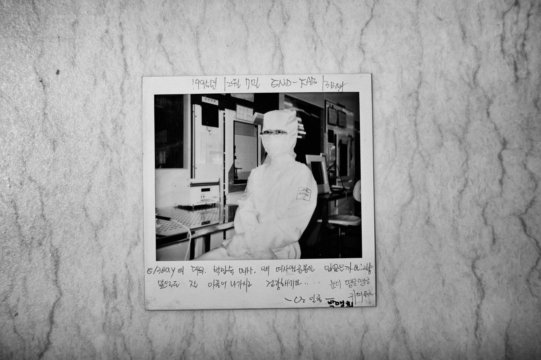 A polaroid picture of Park Min-sook at her working place at 3-bay in Samsung semiconductor factory is seen on a table at her home in Yangpyung, South Korea on Nov. 12, 2013. The picture was taken by Min-sook's colleague on Dec. 7, 1995. Park Min-sook worked at Samsung Electronics semiconductor factory from 1991 to 1998. She was diagnosed with breast cancer in 2012, underwent surgery and is in the convalescent stage.