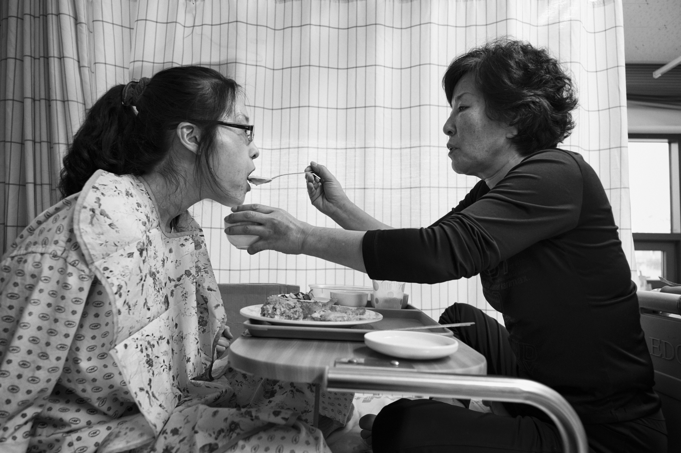 Han Hye-kyung has lunch with help from Kim Shi-nyeo, her mother on her bed at Kangwon National University Hospital in Chuncheon, Gang-won province, South Korea on Mar. 7, 2013