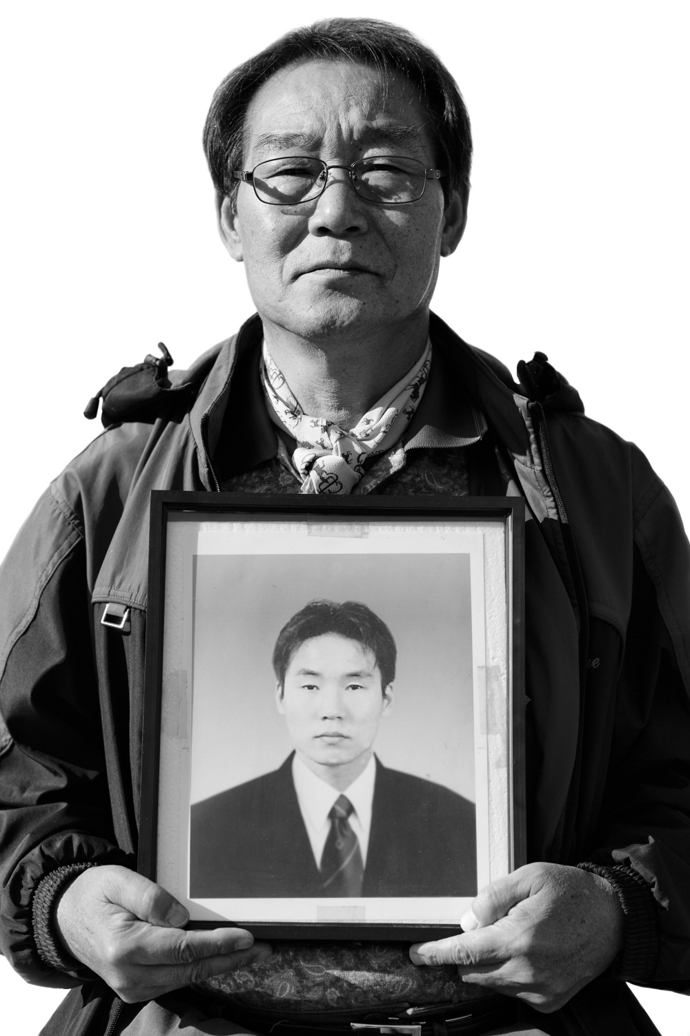 Park Hyung-jip holds a portrait of his deceased son Park Jin-hyuk in Ulsan, South Korea on Nov. 5, 2013. Park Jin-hyuk, only one son of Park Hyung-jip, died of leukemia on November 2005. He worked at Samsung SDI factory in Ulsan, South Korea in 2004.
