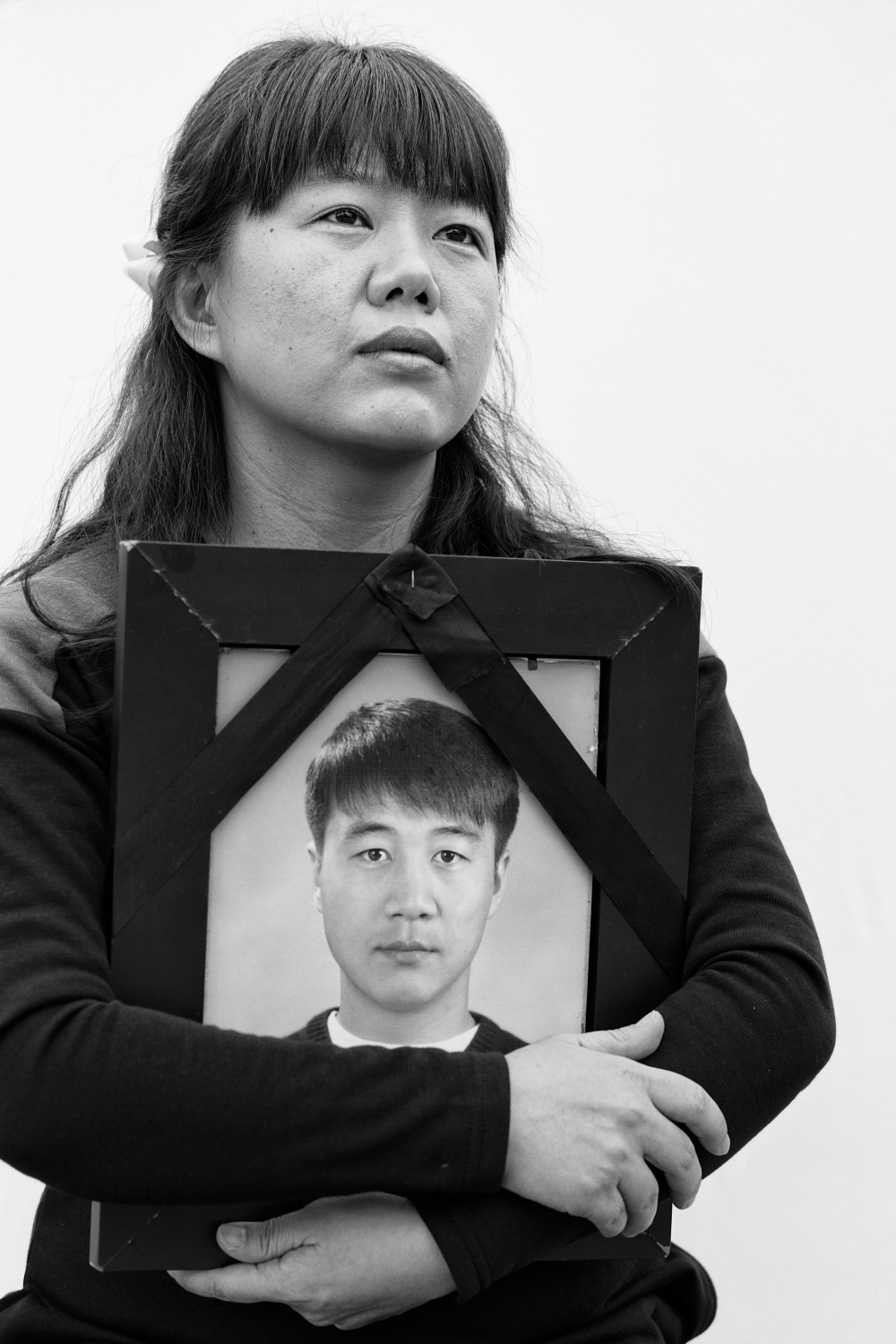 Jung Ae-jung holds the picture of her late husband Hwang Min-woong in Bucheon, South Korea on Nov. 9, 2013. Jung Ae-jung and Hwang Min-woong, her husband worked together at Samsung Electronics factory. Hwang worked at the factory from 1997 to 2002 and died of acute lymphocytic leukemia in 2004.