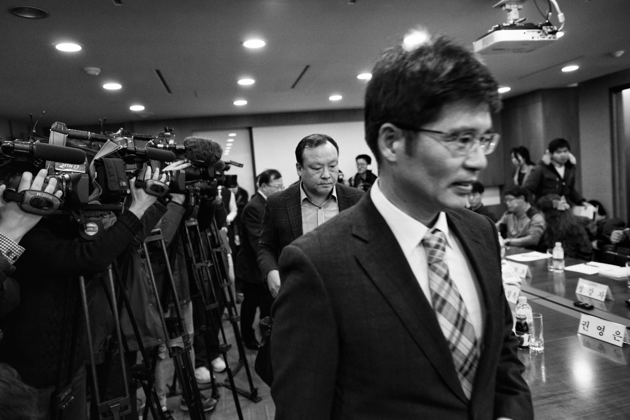 "Baek Su-hyun and Choi Wan-woo, members of Samsung Electronics enter the conference room at the office of a law firm ""Jipyong"" to join the compensation council meeting for victims of Samsung Electronics semiconductor chips and display factories on Jan. 16, 2015 in Seoul, South Korea. The victims, Banolim and Samsung Electronics started negotiation for settlement since 2013. After months of tedious meetings and arguments, they agreed to organize the coordination committee from the third party and authorize the committee to proceed the negotiation in October 2014. The committee suggested the first draft of the compensation plan at the meeting, but none of the parties accepted the offer. After the meeting, on September 2015 Samsung Electronics announced to launch their compensation package for the victims independently in disregard of the year-long meeting with the coordination committee and victims' family members."