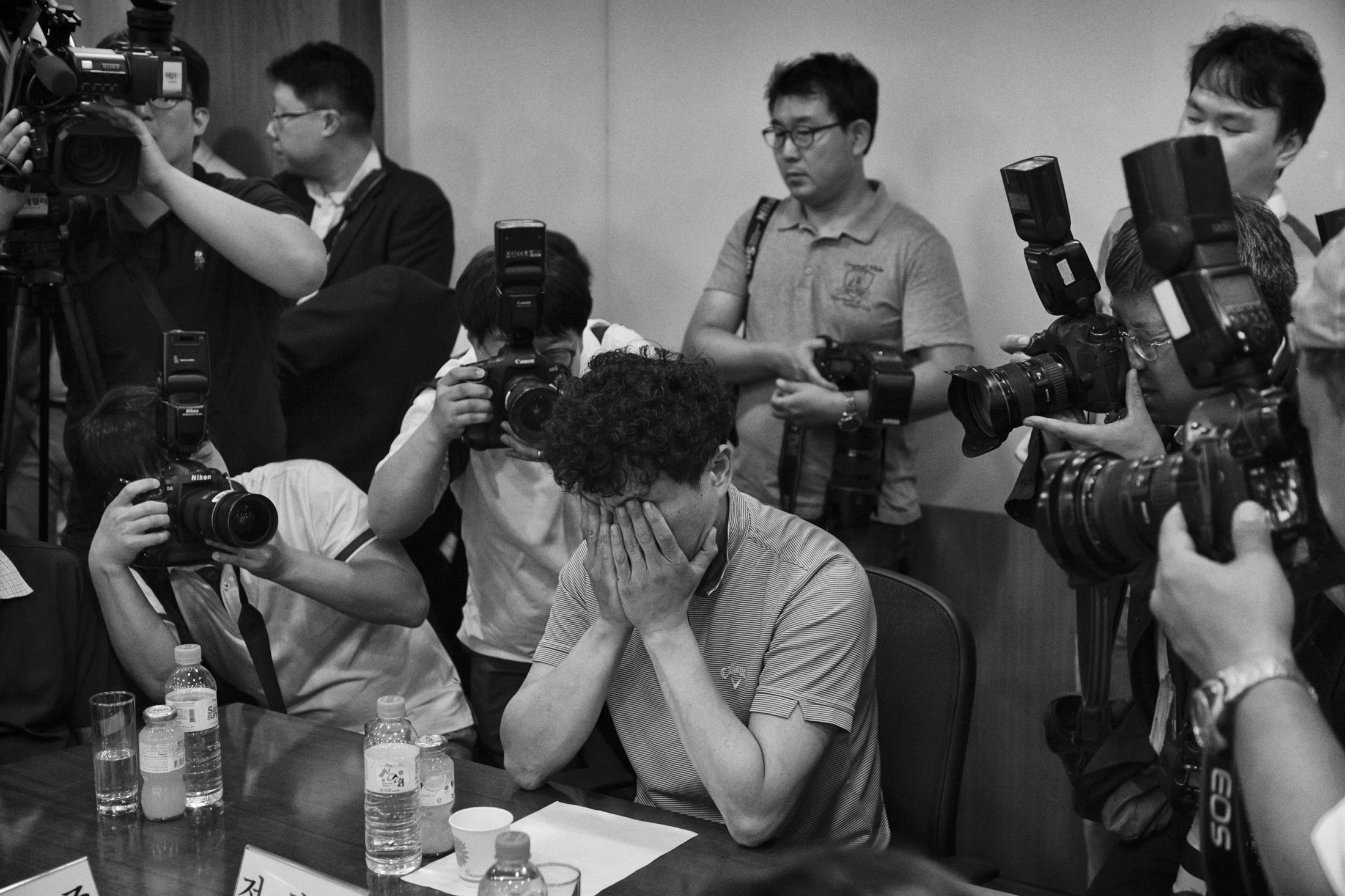 "Chung Hee-su holds his face before the compensation council meeting for victims of Samsung Electronics semiconductor chip and display factories at the office of a law firm ""Jipyong"" on Jul. 23, 2015 in Seoul, South Korea."