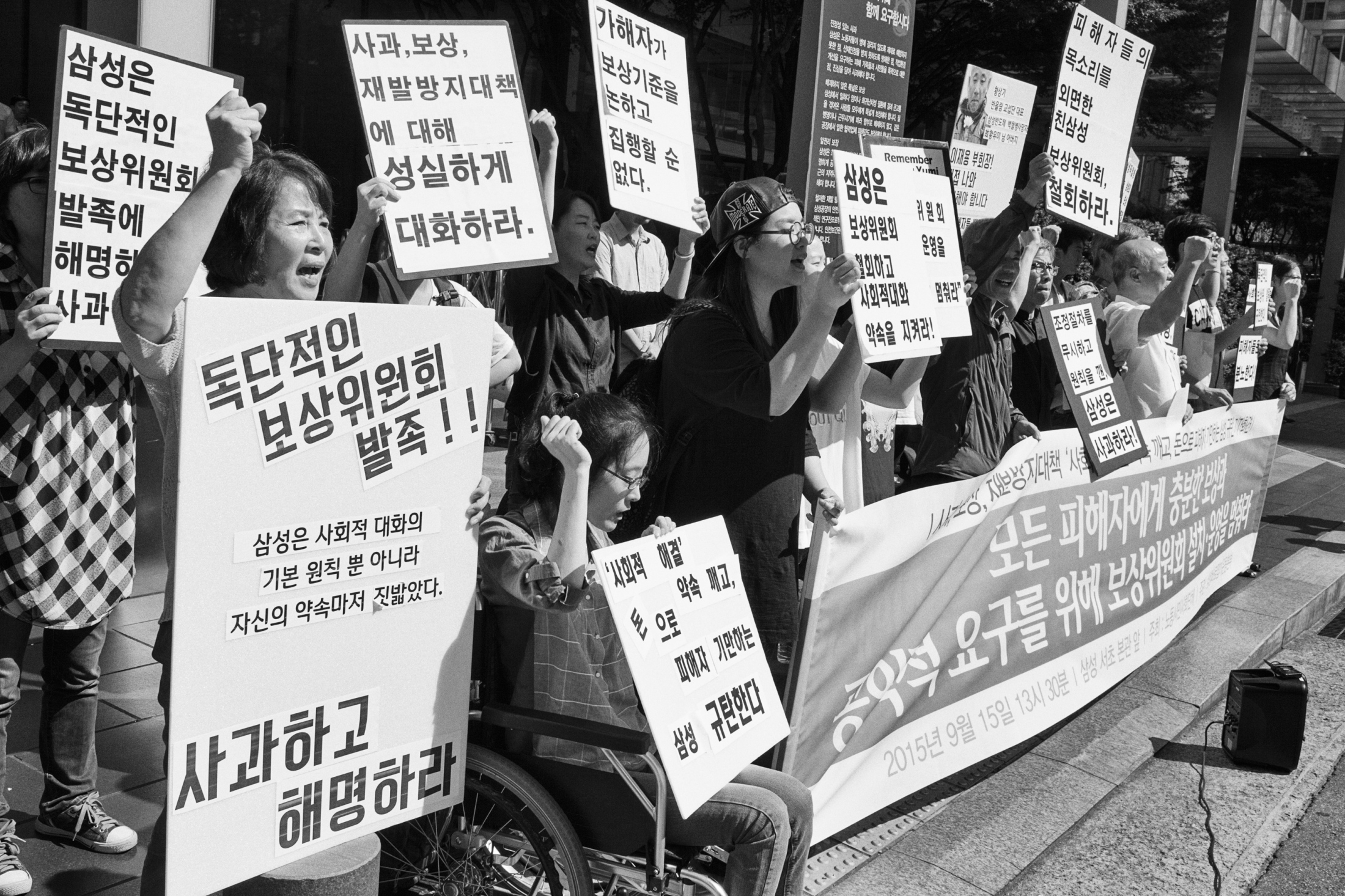 Han Hye-kyung on a wheelchair, her mother Kim Shi-nyeo on her right side, victims' family members and supporters for the victims hold a protest against the company in front of Samsung Town Headquarters on Sep. 15, 2015 in Seoul, South Korea. The victims, Banolim and Samsung Electronics started negotiation for settlement since 2013. After months of tedious meetings and arguments, they agreed to organize the coordination committee from the third party and authorize the committee to proceed the negotiation in October 2014. The committee suggested the first draft of the compensation plan at the meeting, but none of the parties accepted the offer. After the meeting, on September 2015 Samsung Electronics announced to launch their compensation package for the victims independently in disregard of the year-long meeting with the coordination committee and victims' family members.