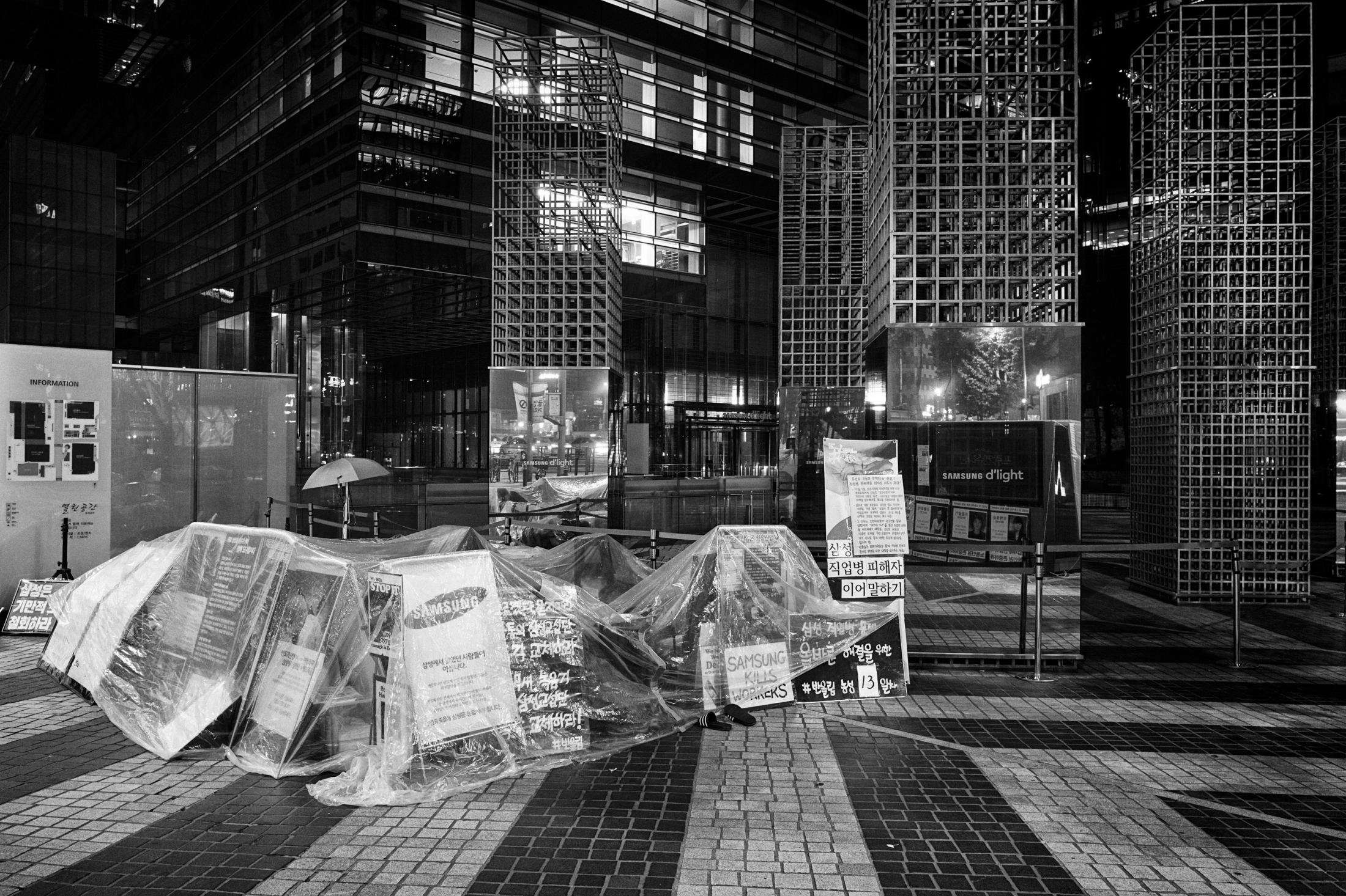 "A protest camp made with plastic covers and cardboard boxes is seen in front of Samsung Town Headquarters in Seoul, South Korea on Oct. 20, 2015. The victims' families and ""Banolim,"" an activist group which supports and helps the victims started a camping protest in front of the entrance of Samsung Town Headquarters in Seoul, South Korea from Oct. 7, 2015, after a compensation negotiation with the company broke down despite nearly three years of effort."