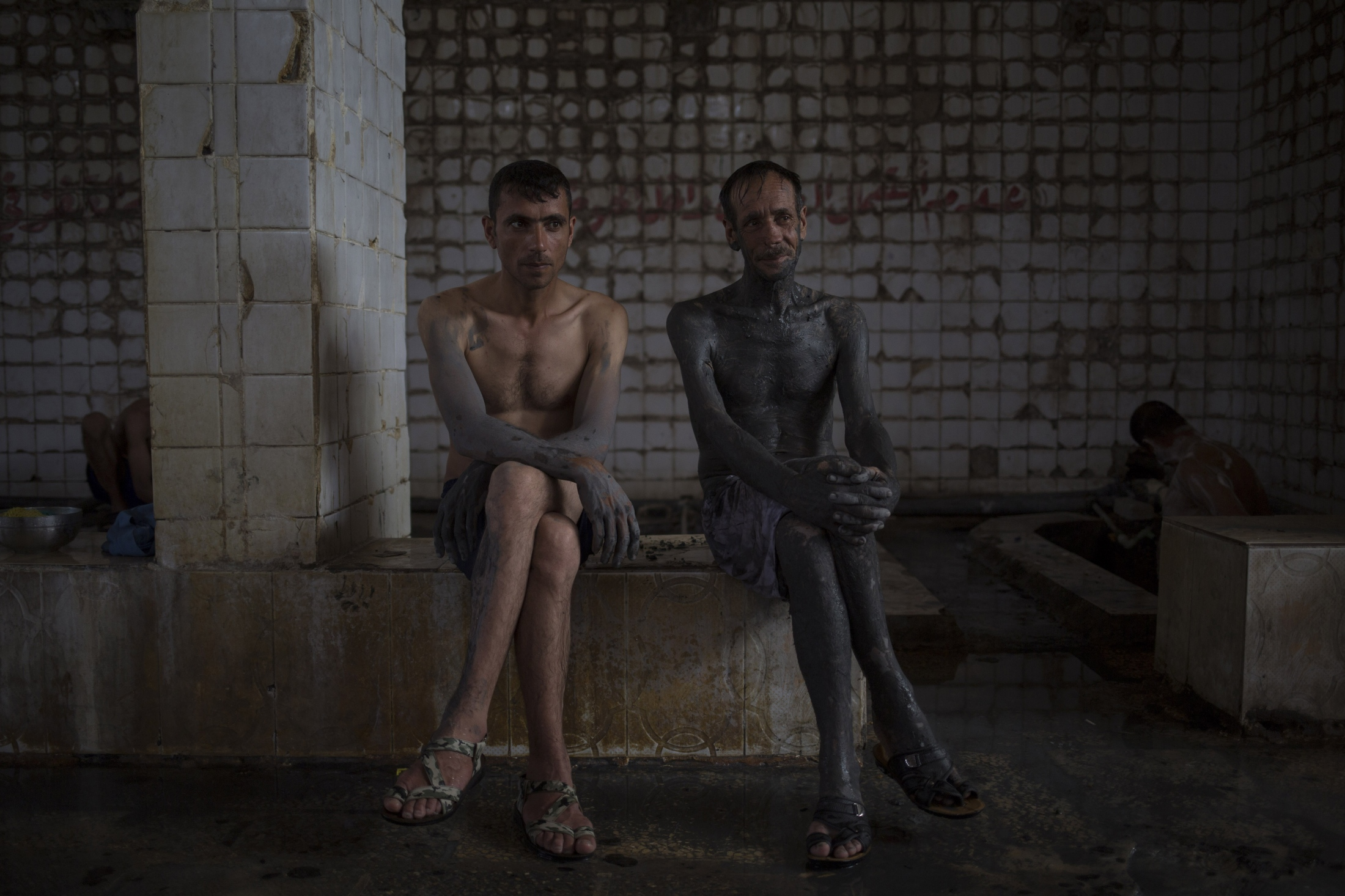 Two customers of the Hamam Alil spa south of Mosul, Iraq, take a break from bathing after covering themselves with mud from a nearby sulphur well, Thursday, April 27, 2017. The mud is supposedly healthy for the skin.