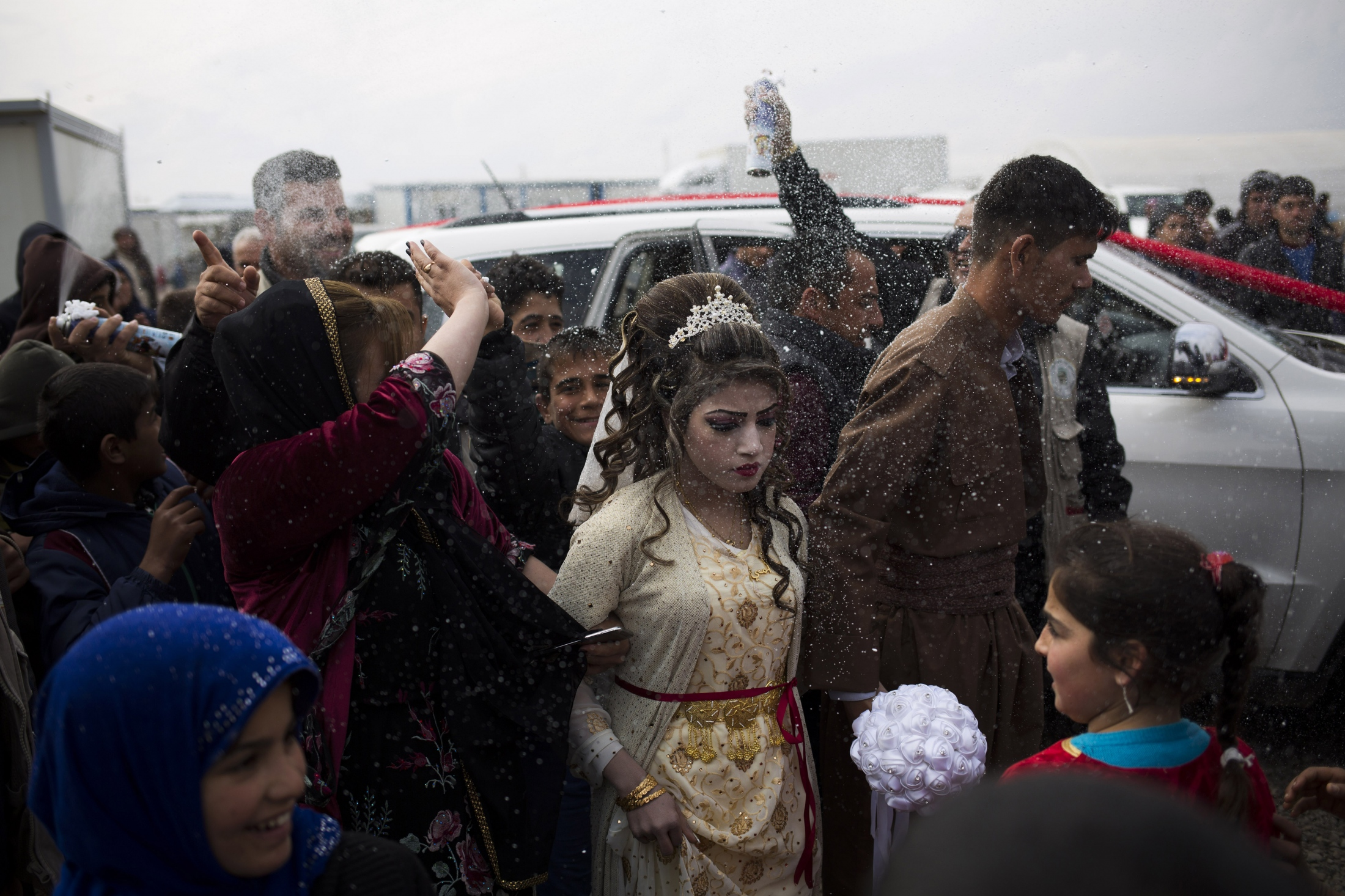 Hussein Zeino Danoon (25) and Shahad Ahmed Abed (16) arrive at the Khazer camp for displaced from Mosul for their wedding. The legal age for marriage in Iraq is 18, or 15 with parental permission. The two celebrated their wedding less than a month after fleeing the fighting in Mosul.