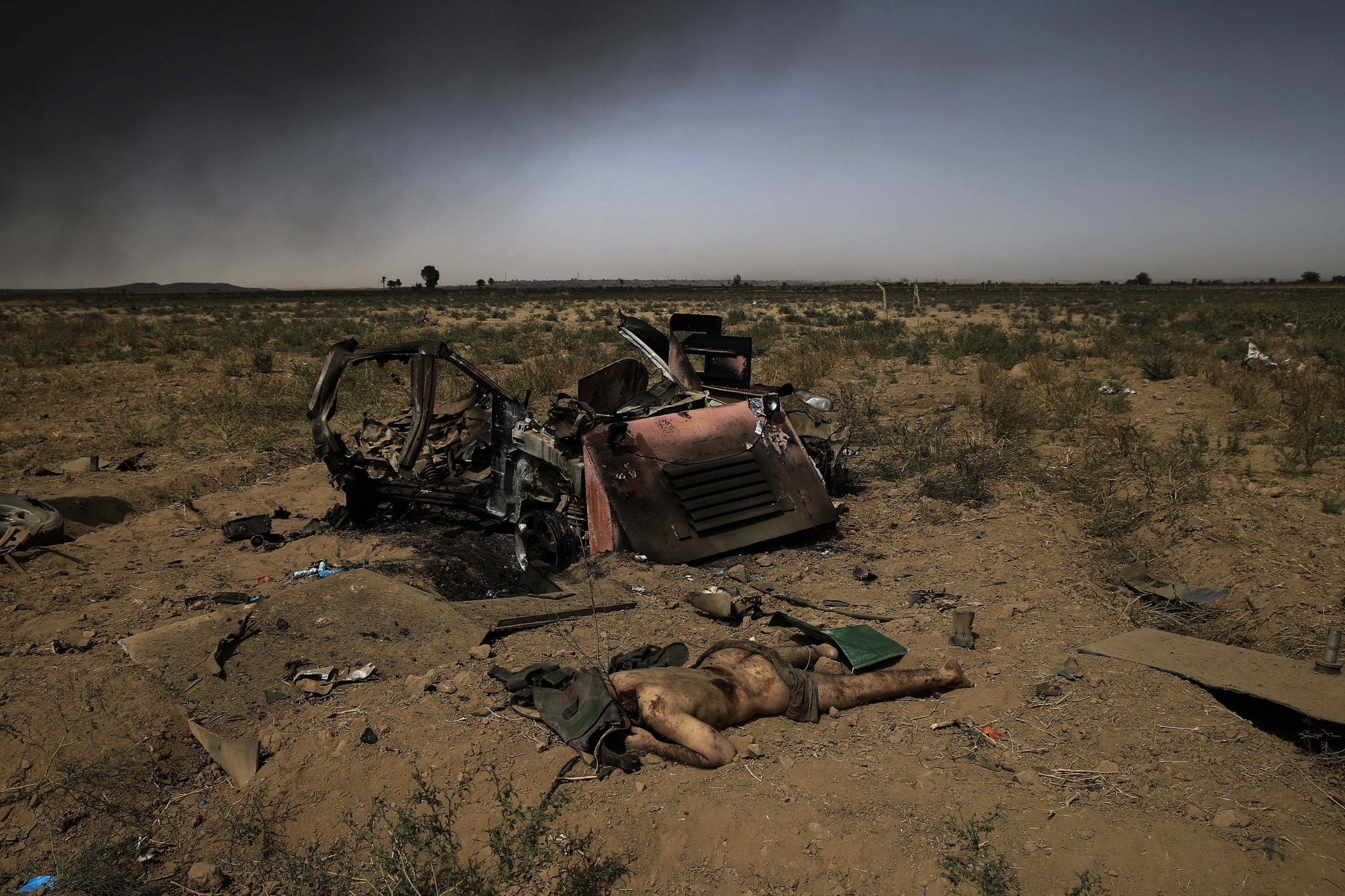 The decapitated body of an IS member lays on the roadside on the frontline in Qayarah, Iraq. Weeks after the liberation of the town, multiple suicide attacks were repelled by the Iraqi army. Villagers of the town took revenge on a captured IS member for their two years oppression while living under the militants' rule. The villagers killed and decapitated the IS member and took his clothes of to humiliate him.