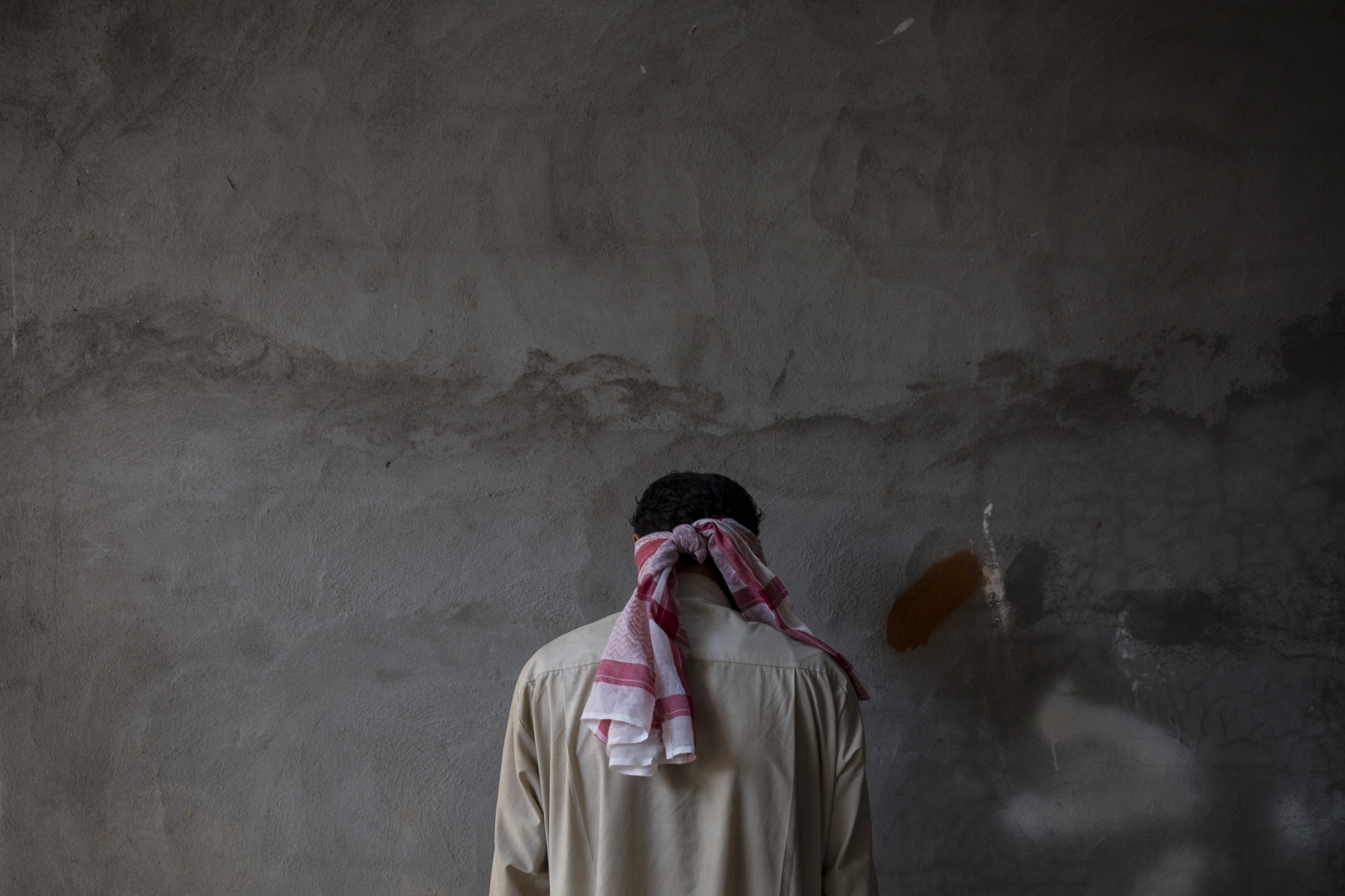 A blindfolded Islamic State suspect stands against a wall at a Kurdish screening center in Dibis, Tuesday, Oct. 3, 2017. Displaced people from Hawija are brought to the center where men are being separated from the women and children and are investigated for involvement in the Islamic State group.
