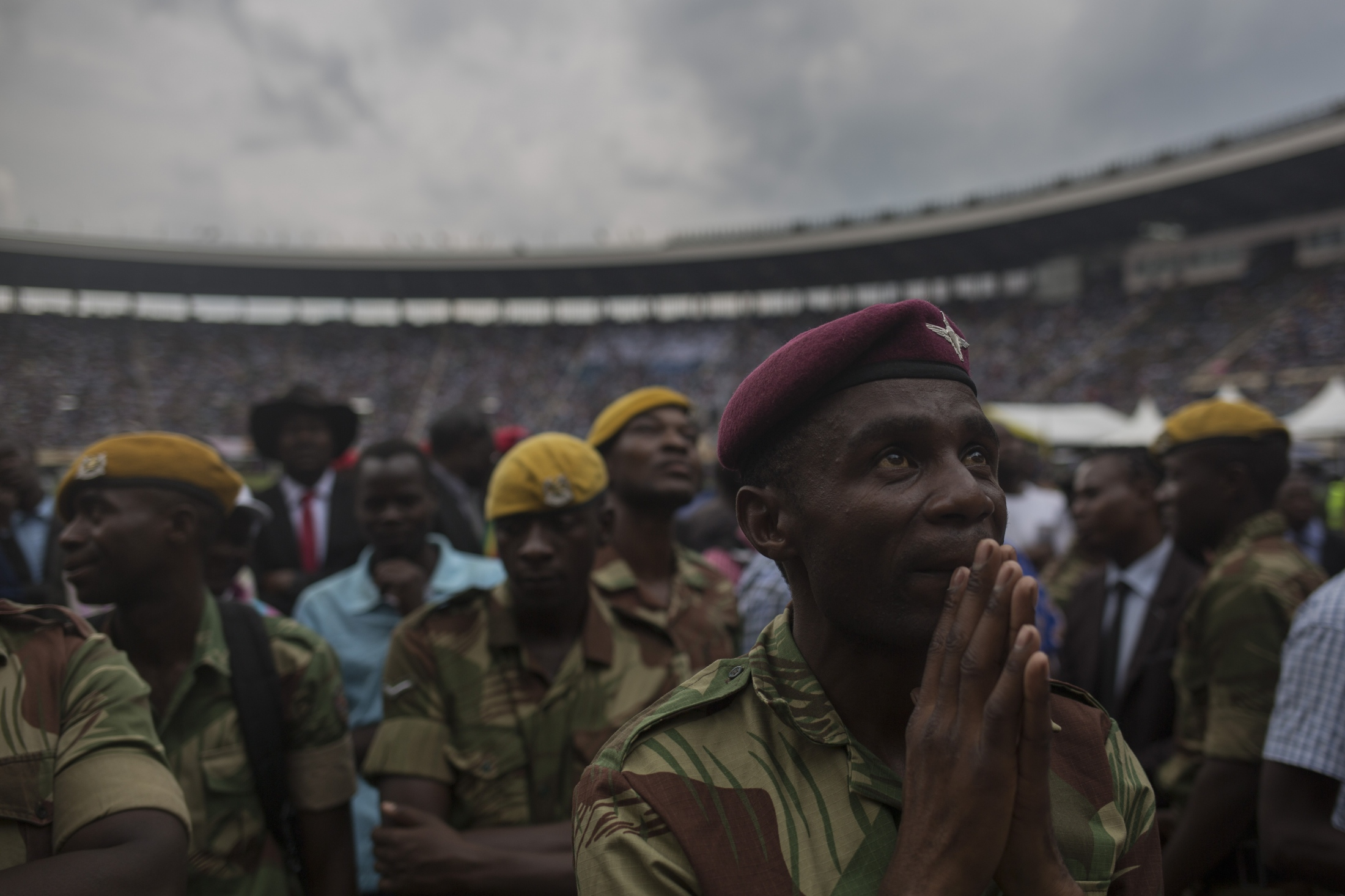 A soldier looks at Zimbabwe's President Emmerson Mnangagwa's speech on a large screen inside the National Sports stadium at the presidential inauguration ceremony in the capital Harare, Zimbabwe Friday, Nov. 24, 2017. Mnangagwa was sworn in as Zimbabwe's president after Robert Mugabe resigned on Tuesday, ending his 37-year rule.