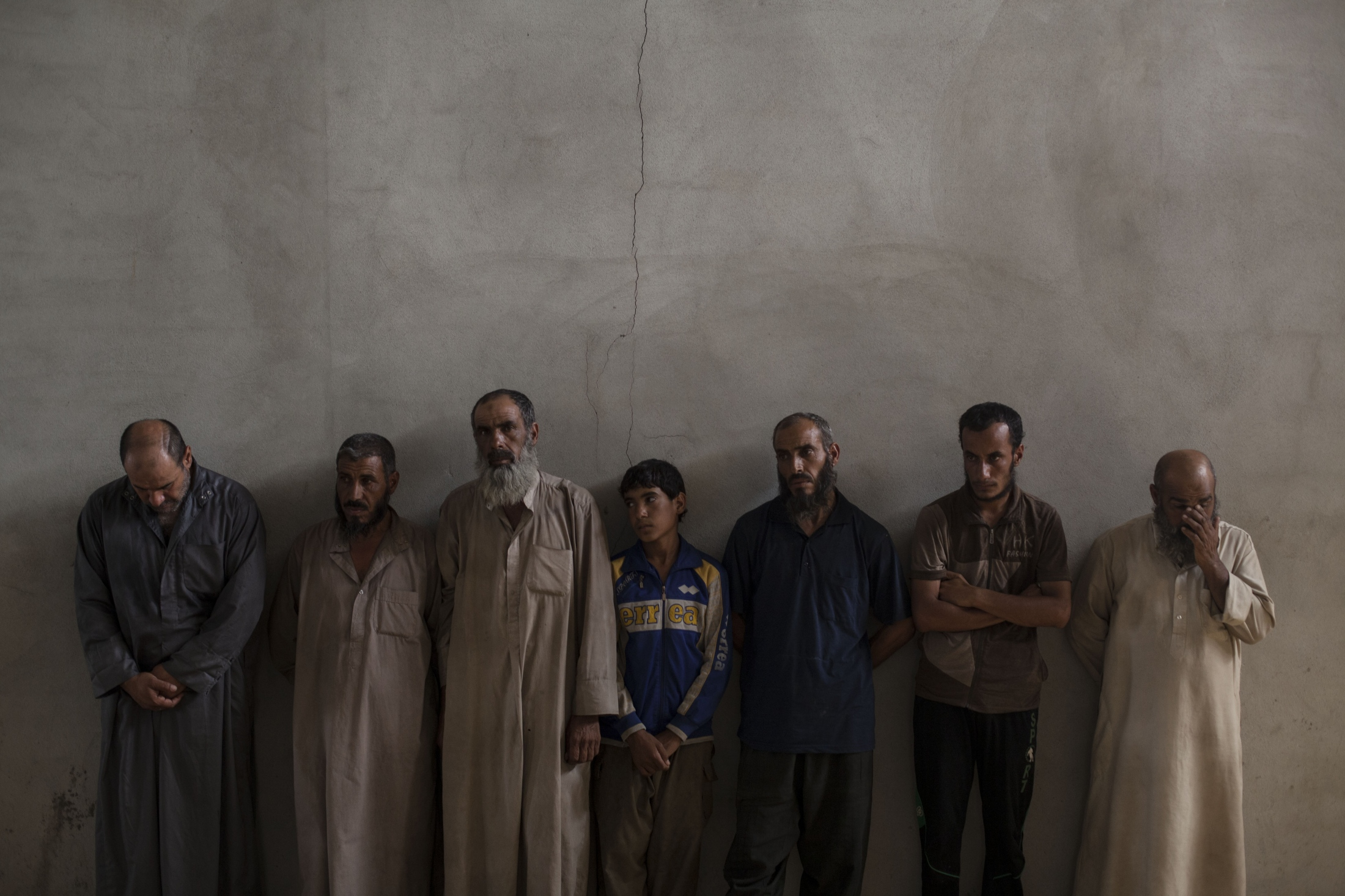 Displaced men from Hawija are lined up against a wall at a Kurdish screening center in Dibis, Tuesday, Oct. 3, 2017. They are brought to the center for a screening process before being moved to camps for displaced people in the Kurdish region of Iraq.