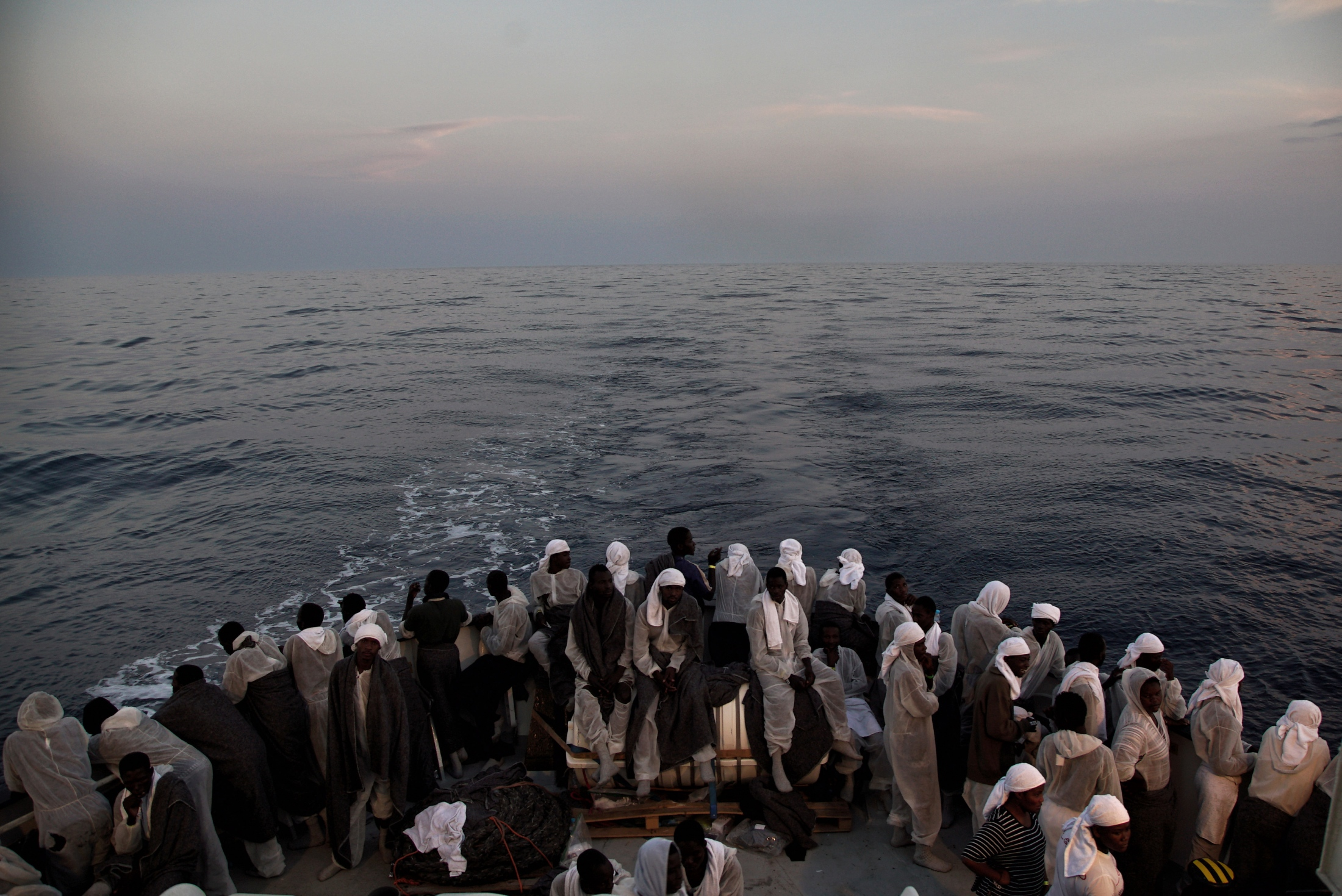 In this Saturday June 25, 2016 file photo, migrants look out from the stern of the 'Aquarius' vessel, on the Mediterranean Sea, with more than 600 migrants aboard the ship rescued by SOS Mediterranee and the medical aid group Medecins Sans Frontieres (MSF). By trying to prevent migrants from taking the dangerous sea journey across the Mediterranean, they are dooming them to prolonged abuse in Libya at the hands of authorities and the country's many militias, rights groups warn.