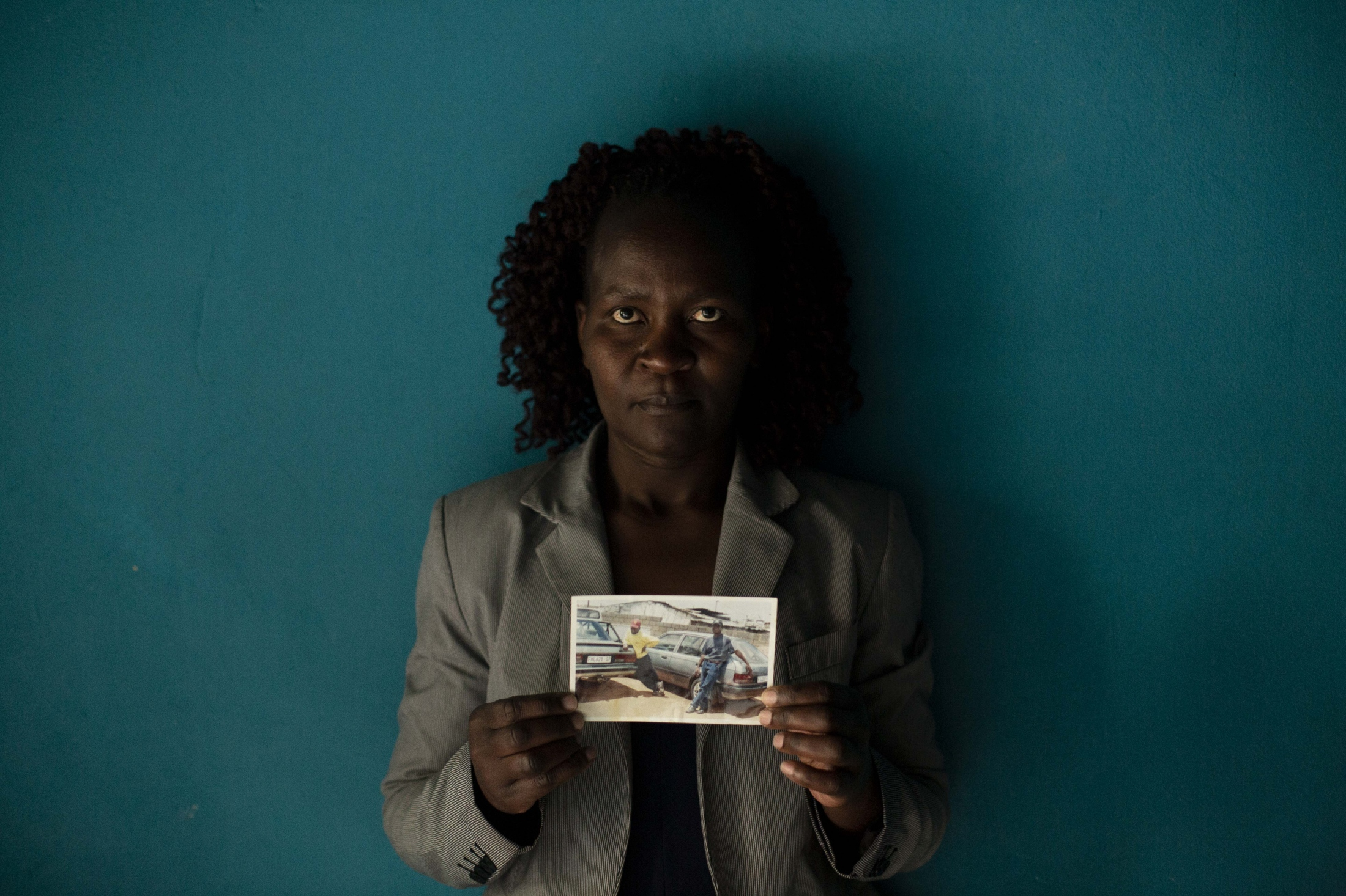 In this Friday, Aug. 24, 2018 photo, Zimbabwean migrant Banele Nkomo holds a photograph of her missing brother, Francis. She doesn't know what happened to him and hasn't from him for years. She says she misses him every day and wants to know whether he passed away and where his body is in order to find closure.