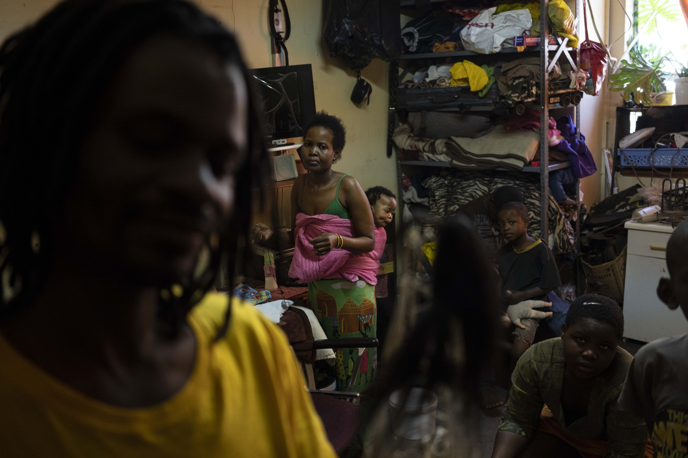 In this Tuesday, Oct. 2, 2018 photo, Zimbabwean migrant Kholakele carries her 6-month old baby in her apartment in Johannesburg. Kholakele and her husband Arnold (left) know stories about missing migrants via friends and relatives. They fear for their five children. If one of them leaves their apartment in Johannesburg downtown for longer than ten minutes, they phone them.