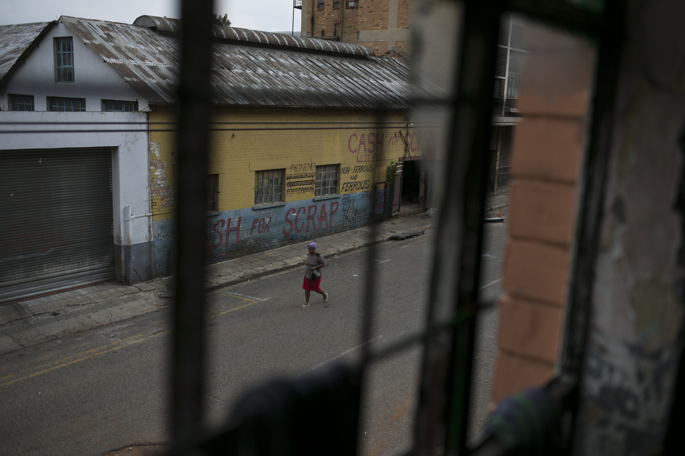 A woman walks past an abandoned building occupied by squatters. March 30, 2018.