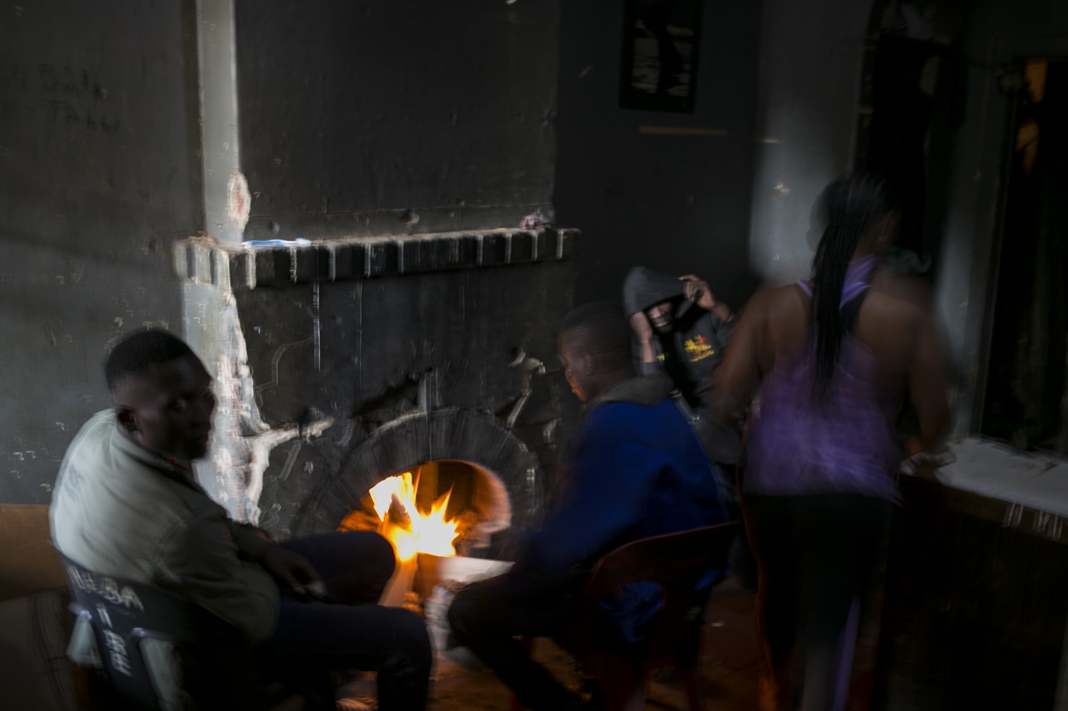 People warm themselves by a fire place in an abandoned building