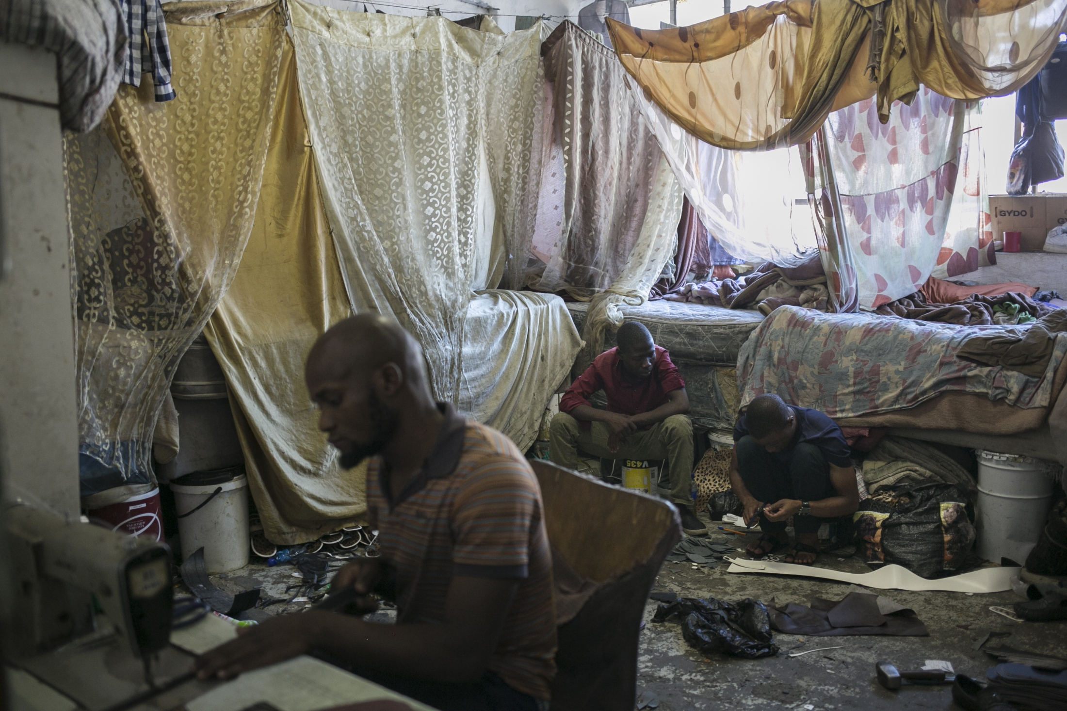 Malawian migrant shoe makers work inside their bedroom. March 29, 2018.