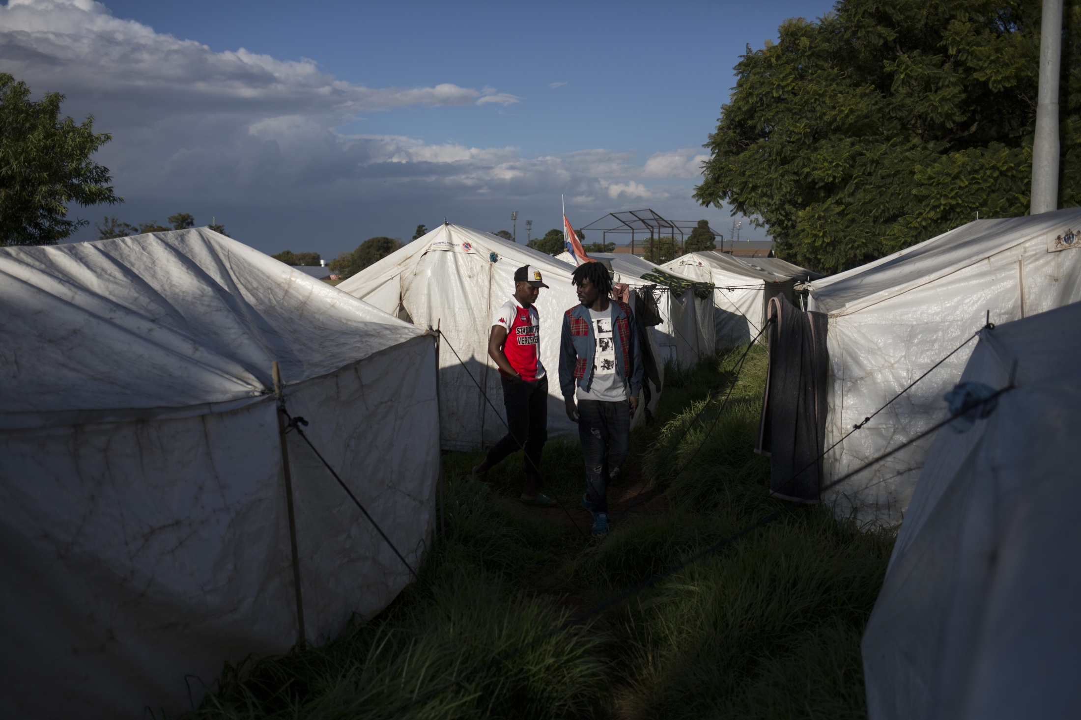 Migrants walk amid tents provided by the city government after they were evicted. April 19, 2018.