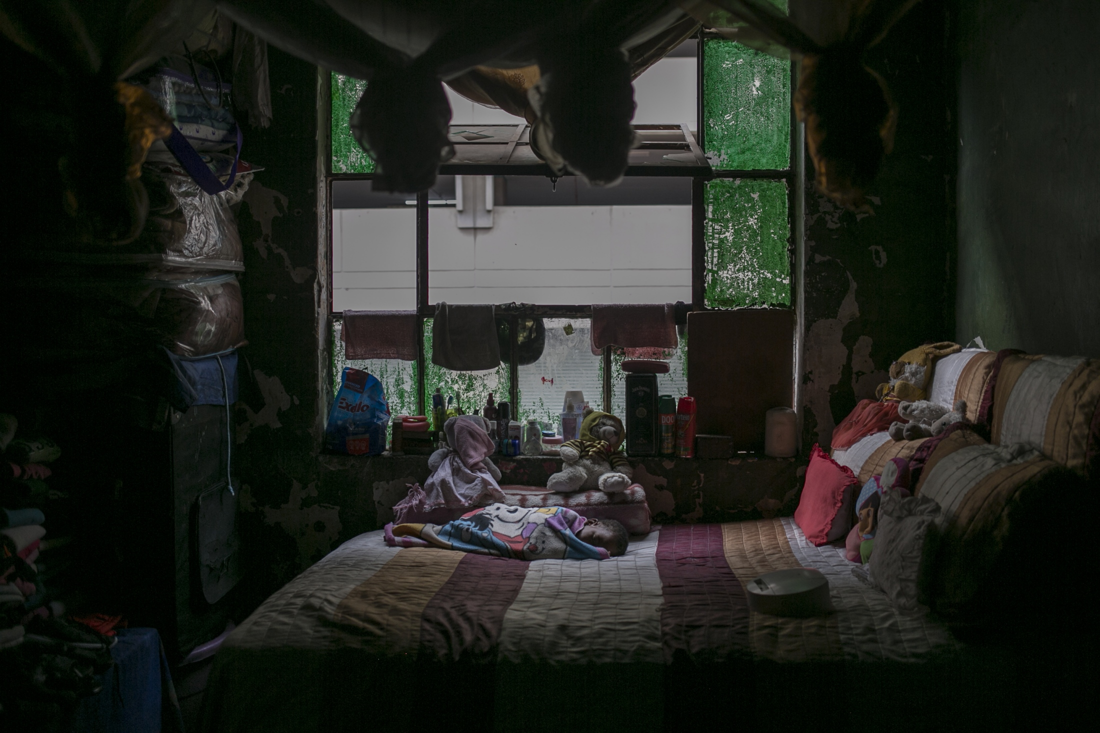 Two-year-old Makanake Angel sleeps on her mother's bed inside an abandoned building. March 30, 2018.