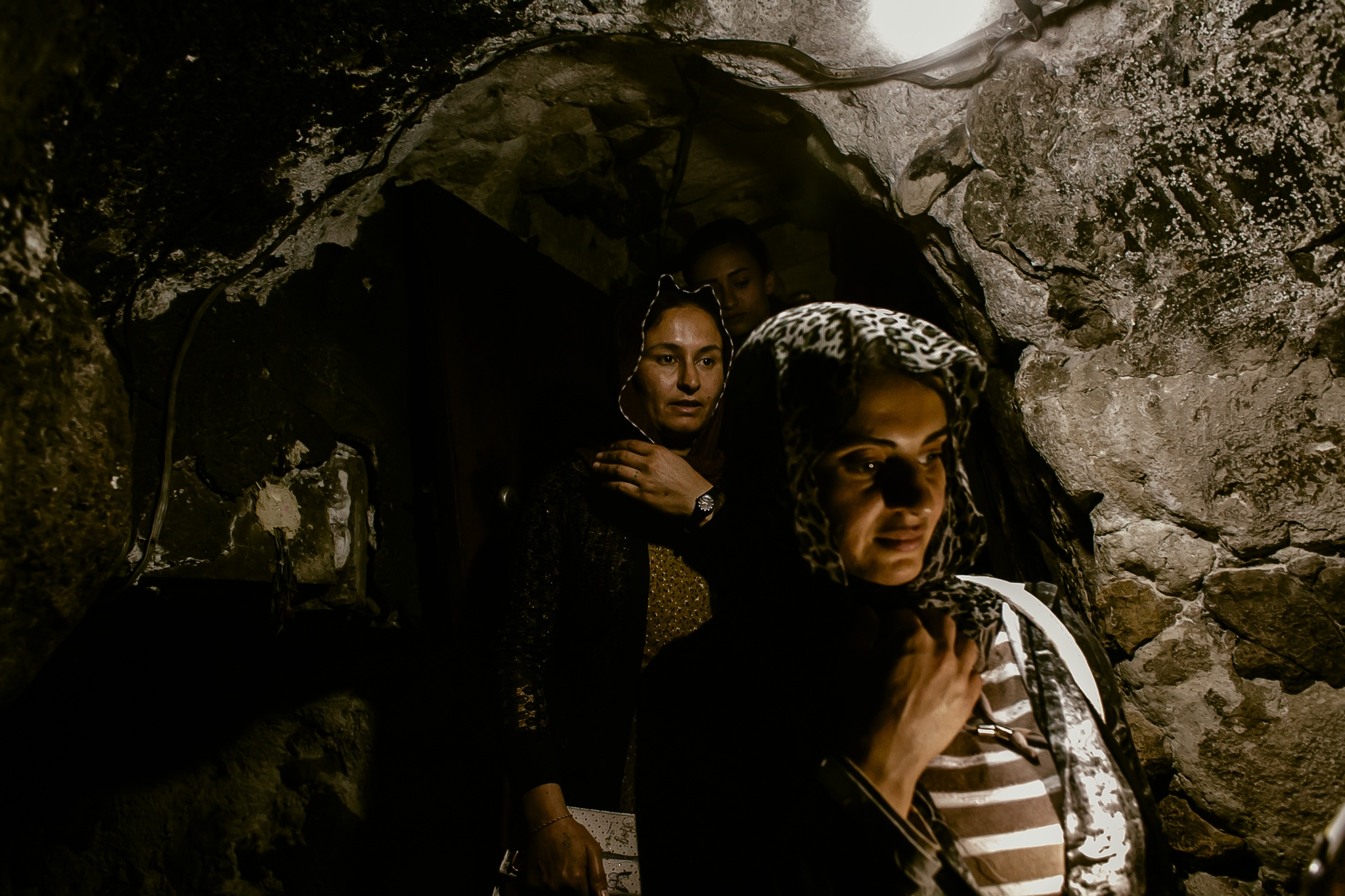 "Ghazal Naser Khalaf (center) and Turkia Hussein (right) descend through a narrow entrance giving access to a sacred fountain called ""Zamzam"". In this place, couples can not enter together because they can be converted into siblings."