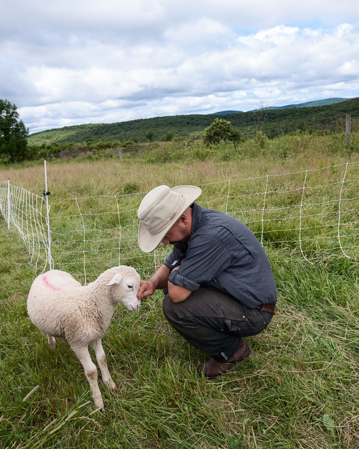 "Farmer James nuzzles his favorite lamb. ""This little fella has the best personality."" I asked him about the challenge of becoming attached to the animals, to which he replied: ""Sometimes it's very hard."""