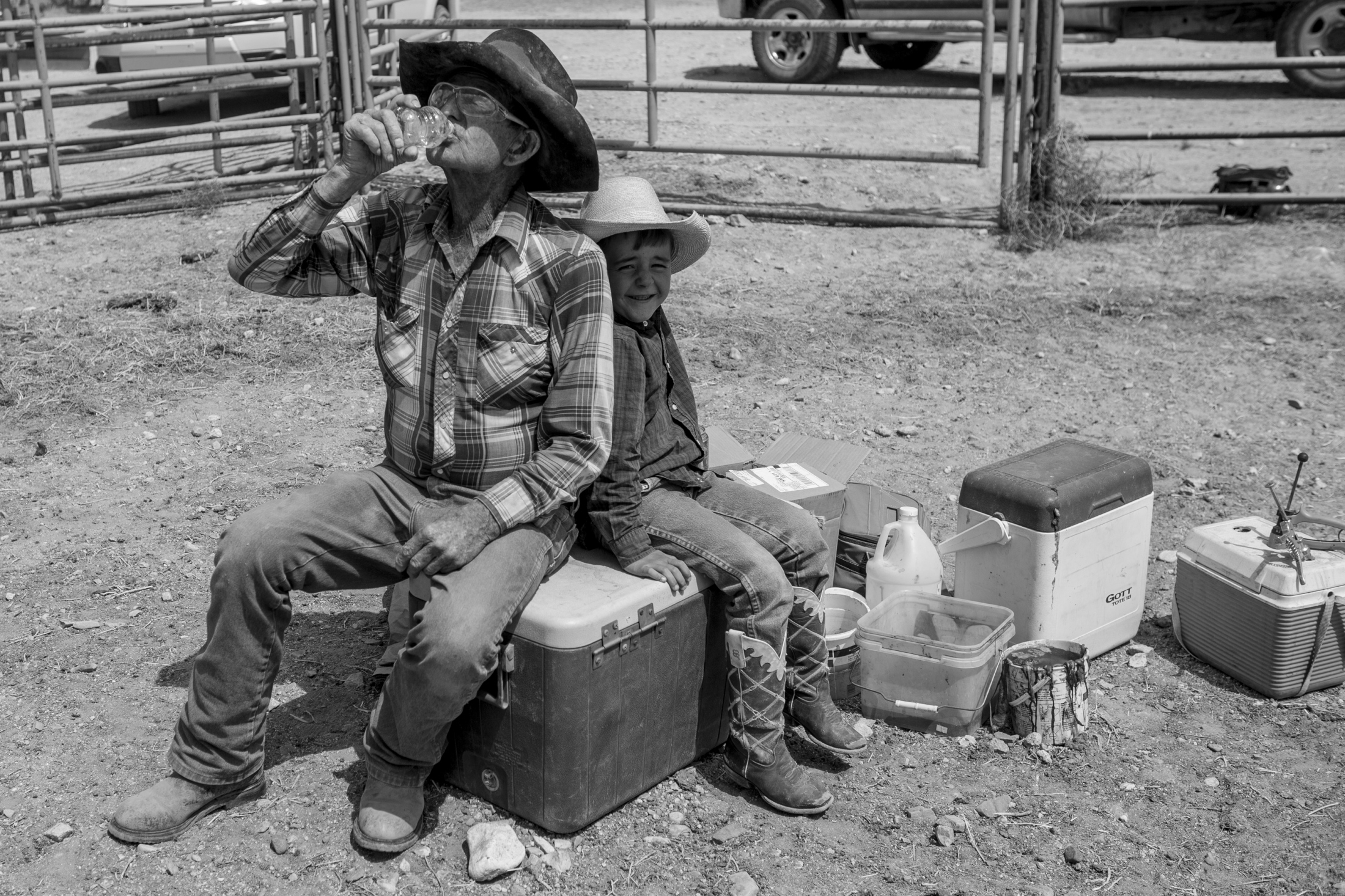 Eighty-two-year-old Bill Wells chugs water while sitting next to his great-grandson Ryan while taking a break from branding in to nearly ninety degree spring heat.