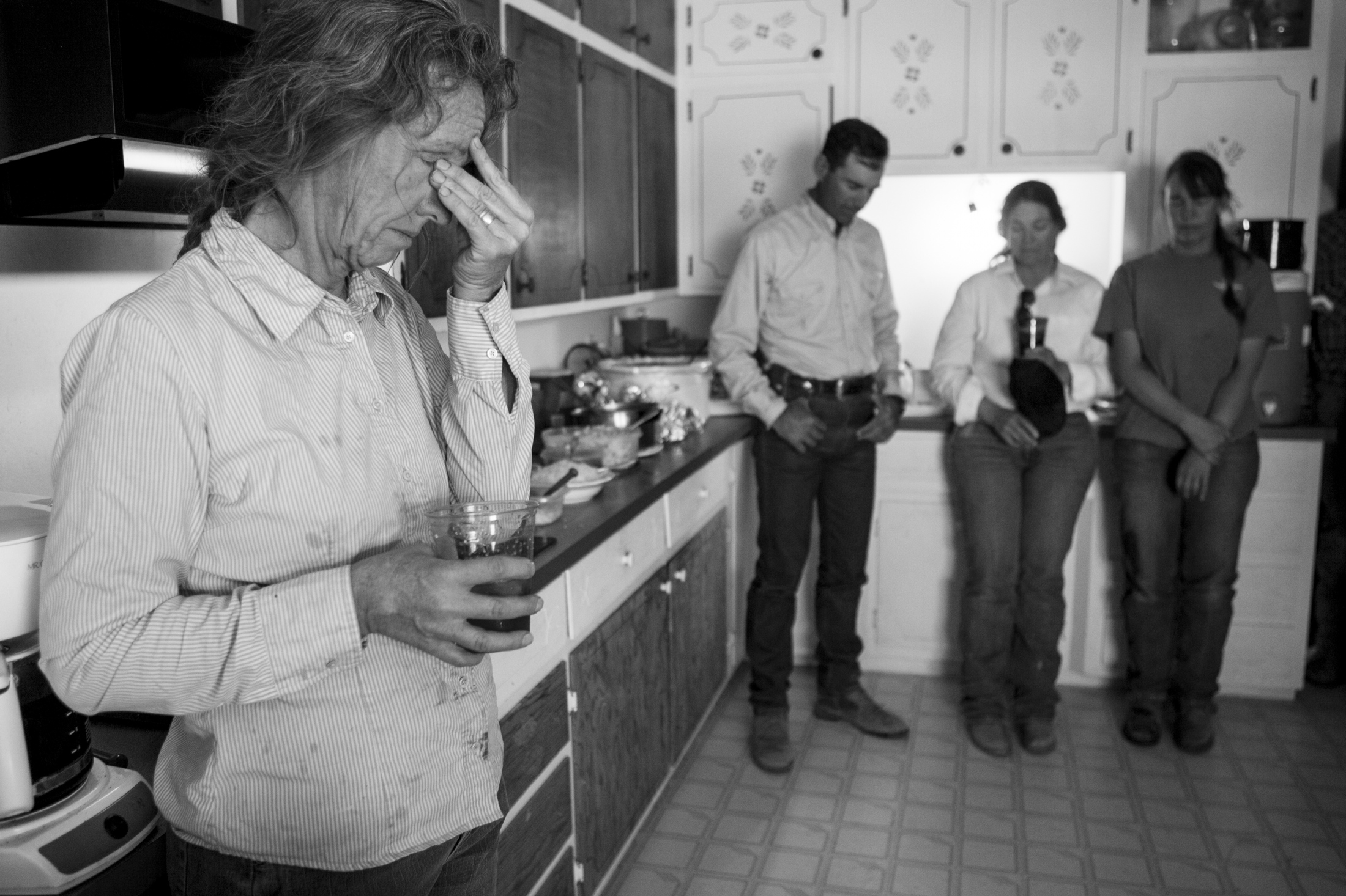 Jimmie Wells presses between her eyes in exhaustion as Ethan Fuchs, Dianne Fuchs and her daughter, Rebecca Wells take a moment to pray before lunch in the ranch house.