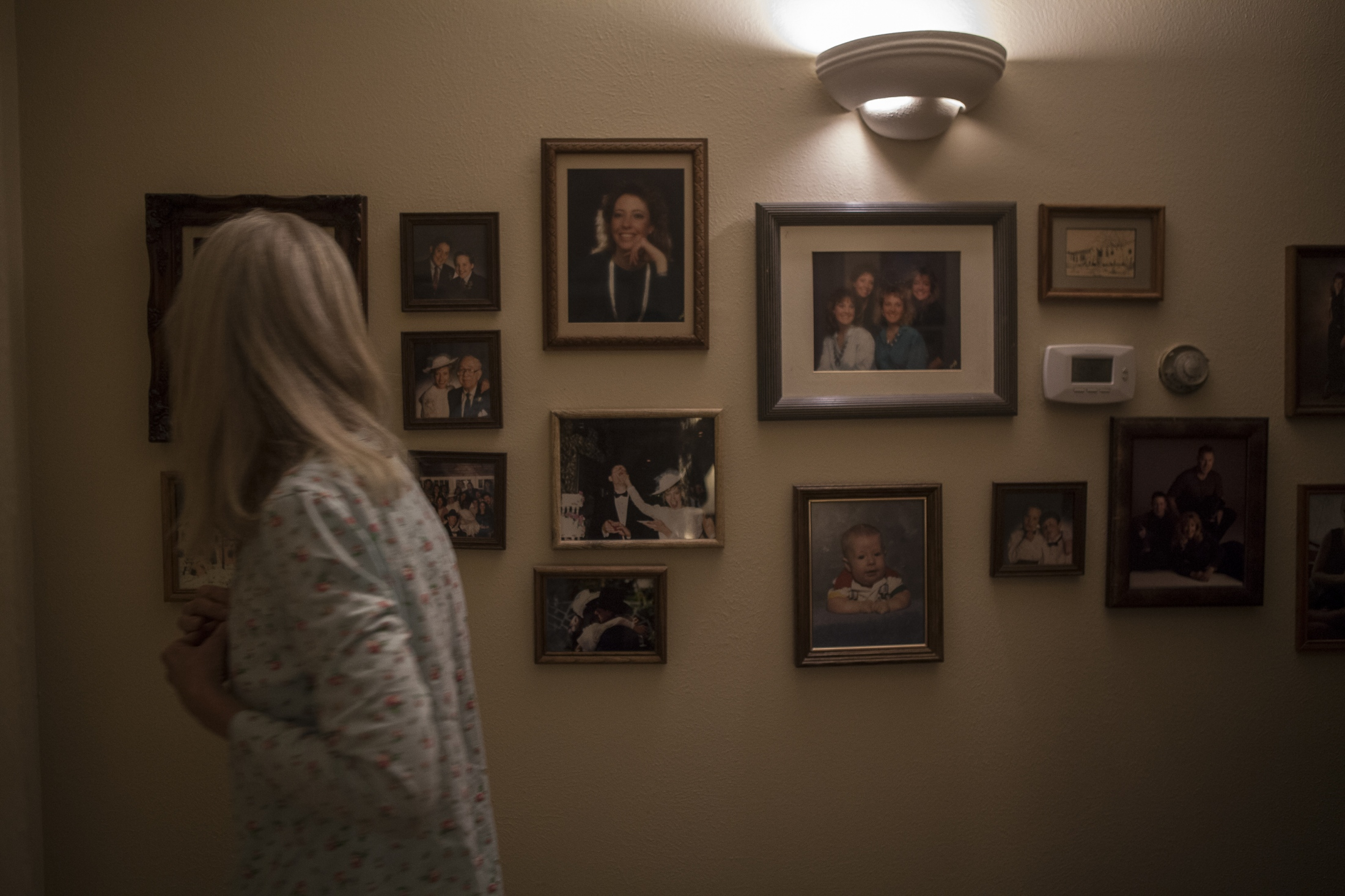Nancy glances at photos of her and her family as she passes through the hallway of her and her husband's home.
