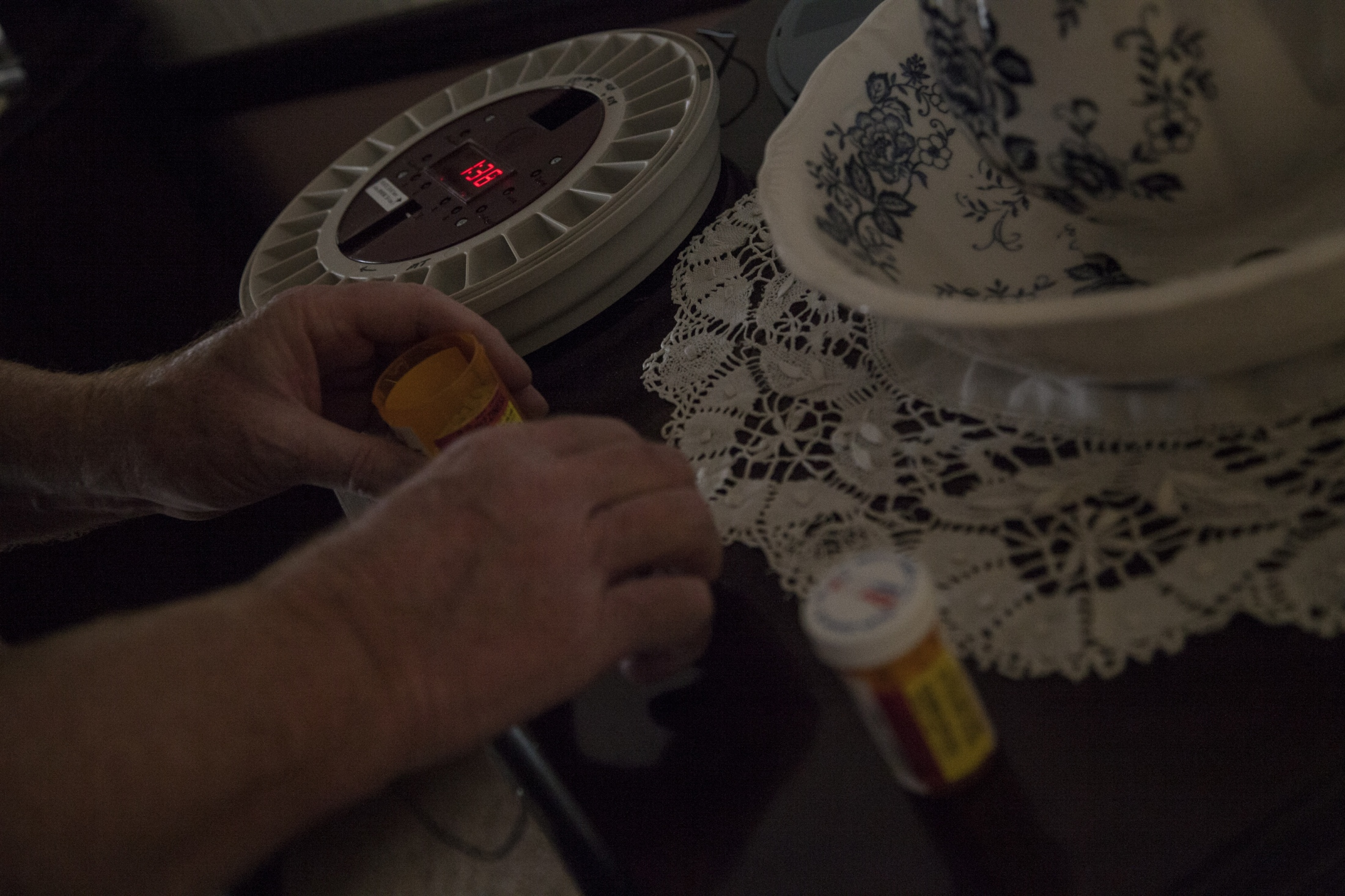 Bill Hinz fills a locked medication box that alerts Nancy's caregiver and family members that she needs to be administered her pills.