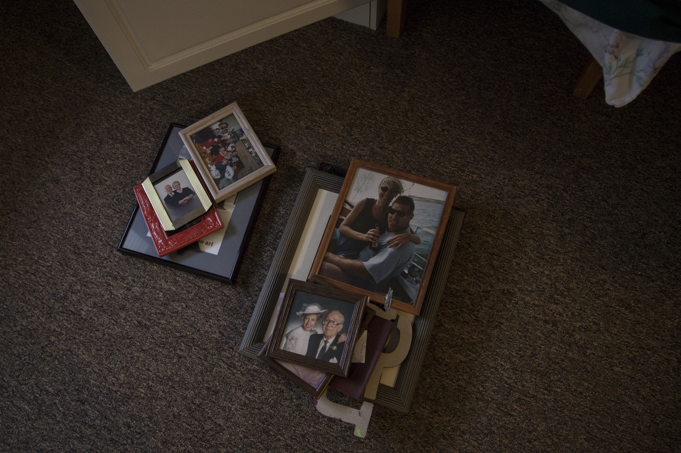 Framed pictures sit on the floor in the senior home as family members move in her personal items.