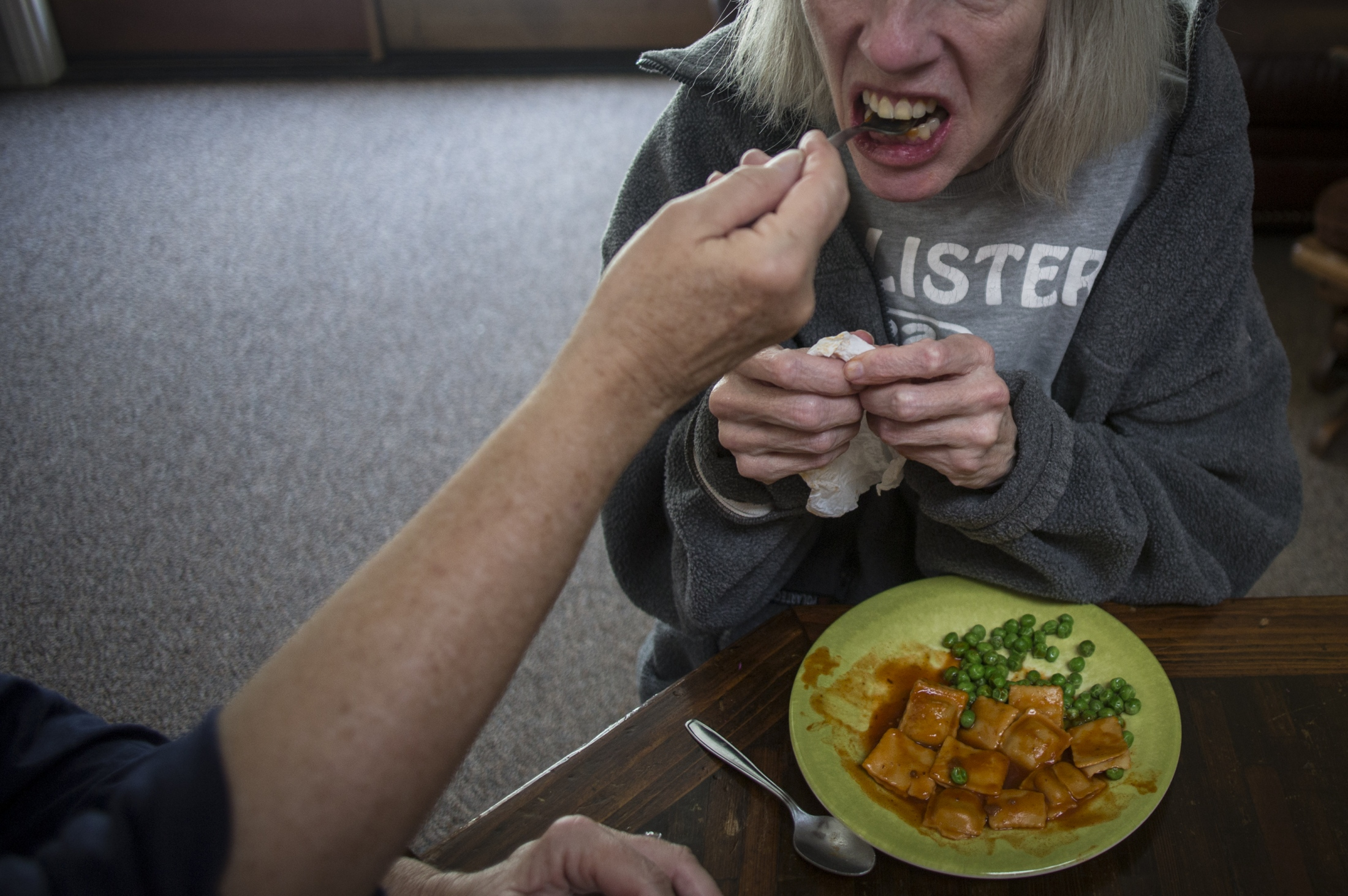 """When her sisters visit, they help to feed her to ensure she gets needed nourishment. Often times Nancy will not eat with a utensil resorting to her hands instead, which bothers the elderly folks at the home. They make remarks such as """"look at her"""" as they shake their heads in disapproval. Though most of the other residents have dementia as well, none of them are as incapable of taking care of themselves as Nancy."""