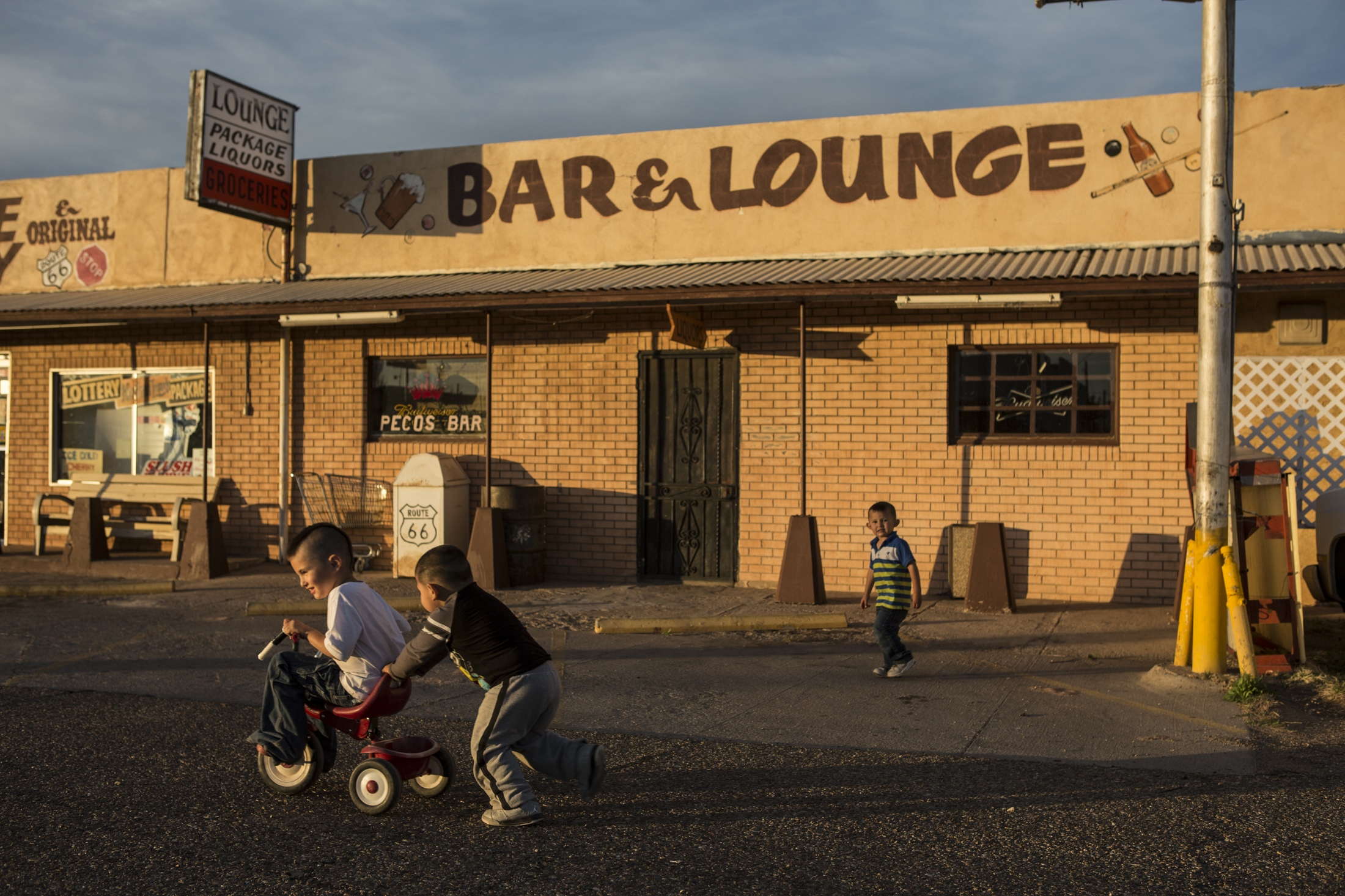 Children play in front of the now closed Pecos Bar on the west side of Santa Rosa. The saloon stopped serving patrons in the winter of 2015 after the owner sold the liquor license to a national restaurant chain in Albuquerque. The bar was a part of the Route 66 boom in the mid 20th-Century when the travelers would first enter the town and drive past the bar. After construction of Interstate 40 diverted traffic from the west side, businesses began to close.