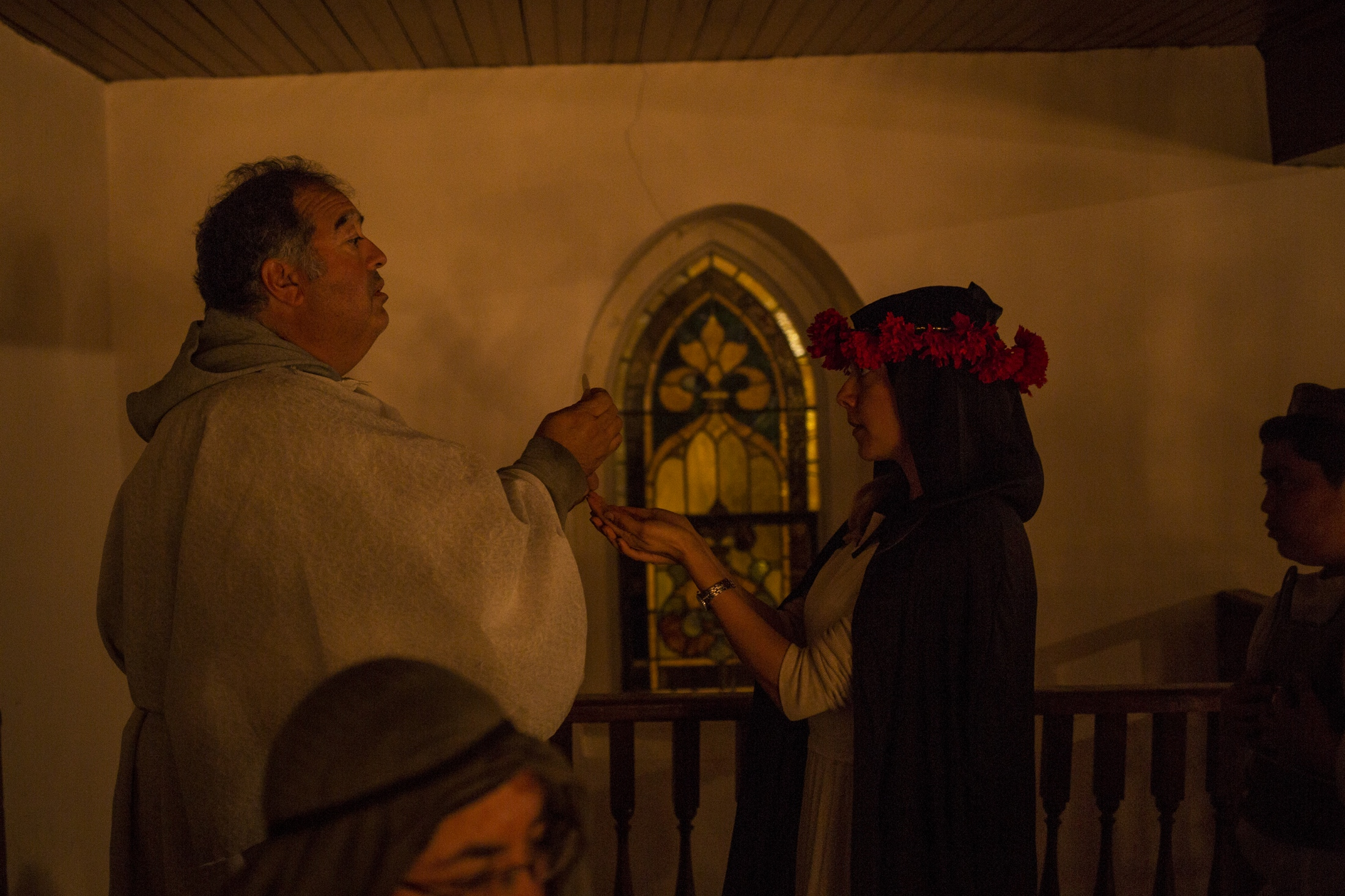 Severiano Sisneros III gives communion to Victoria Flores who is dressed as Saint Rose of Lima during the All Saints Day mass.