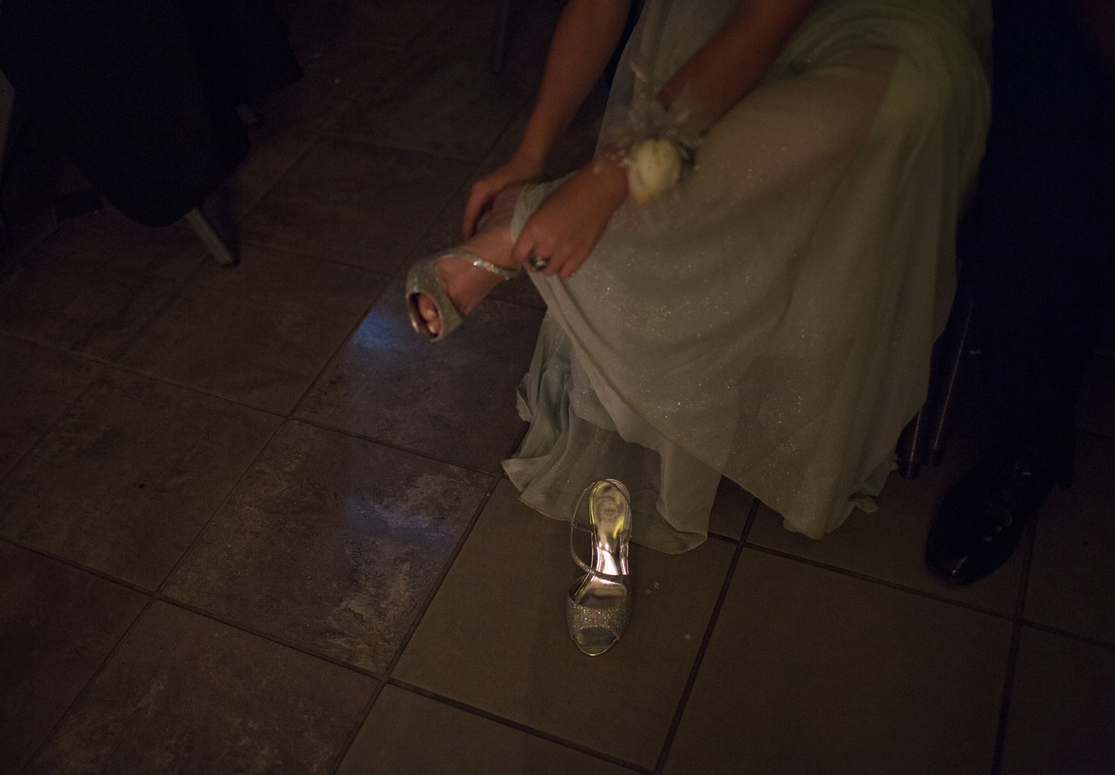 A girl puts on her shoes after taking them off to dance at the homecoming dance.