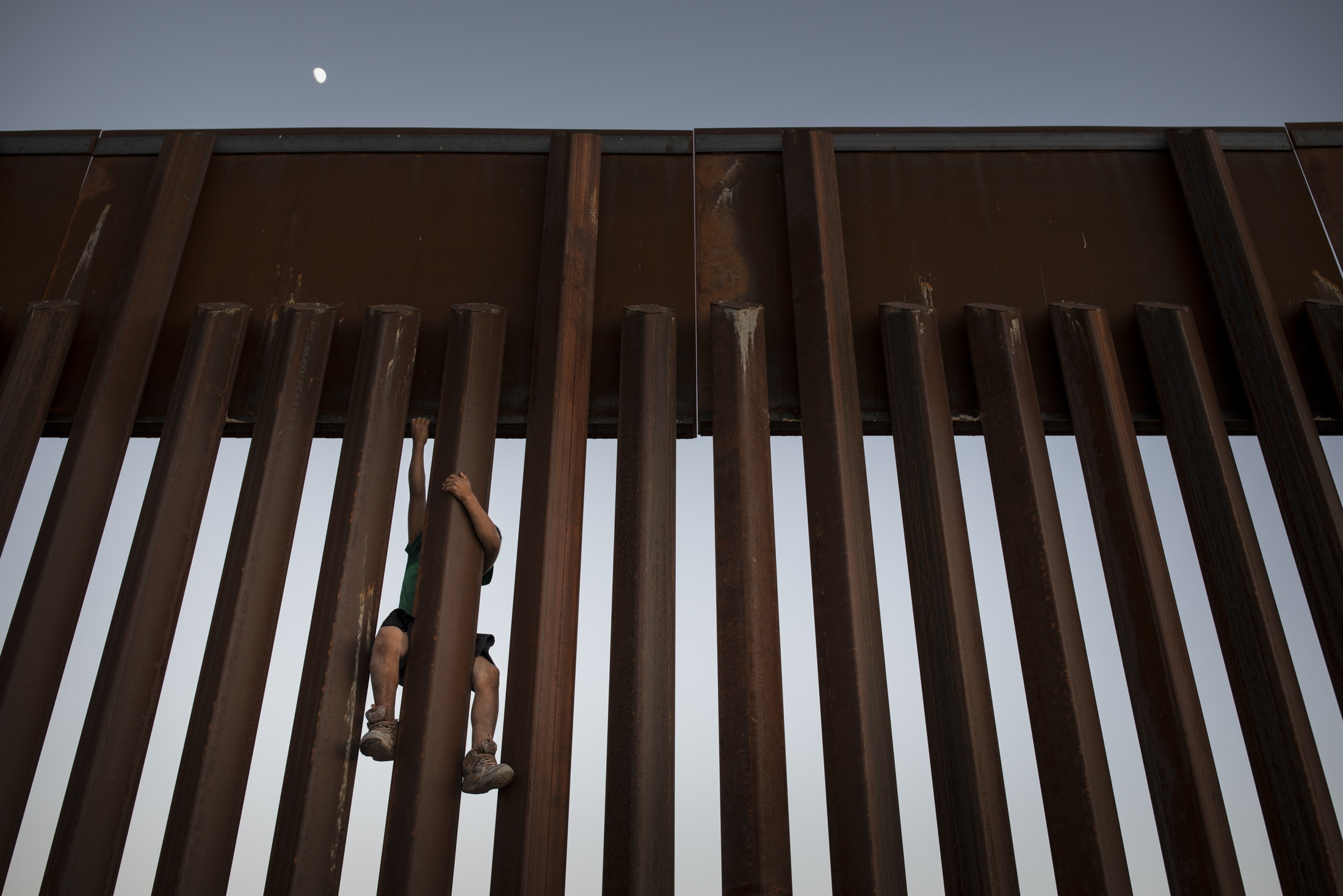 A young boy climbs the border fence for fun where Anapra, Mexico and Sunland Park, New Mexico meet.
