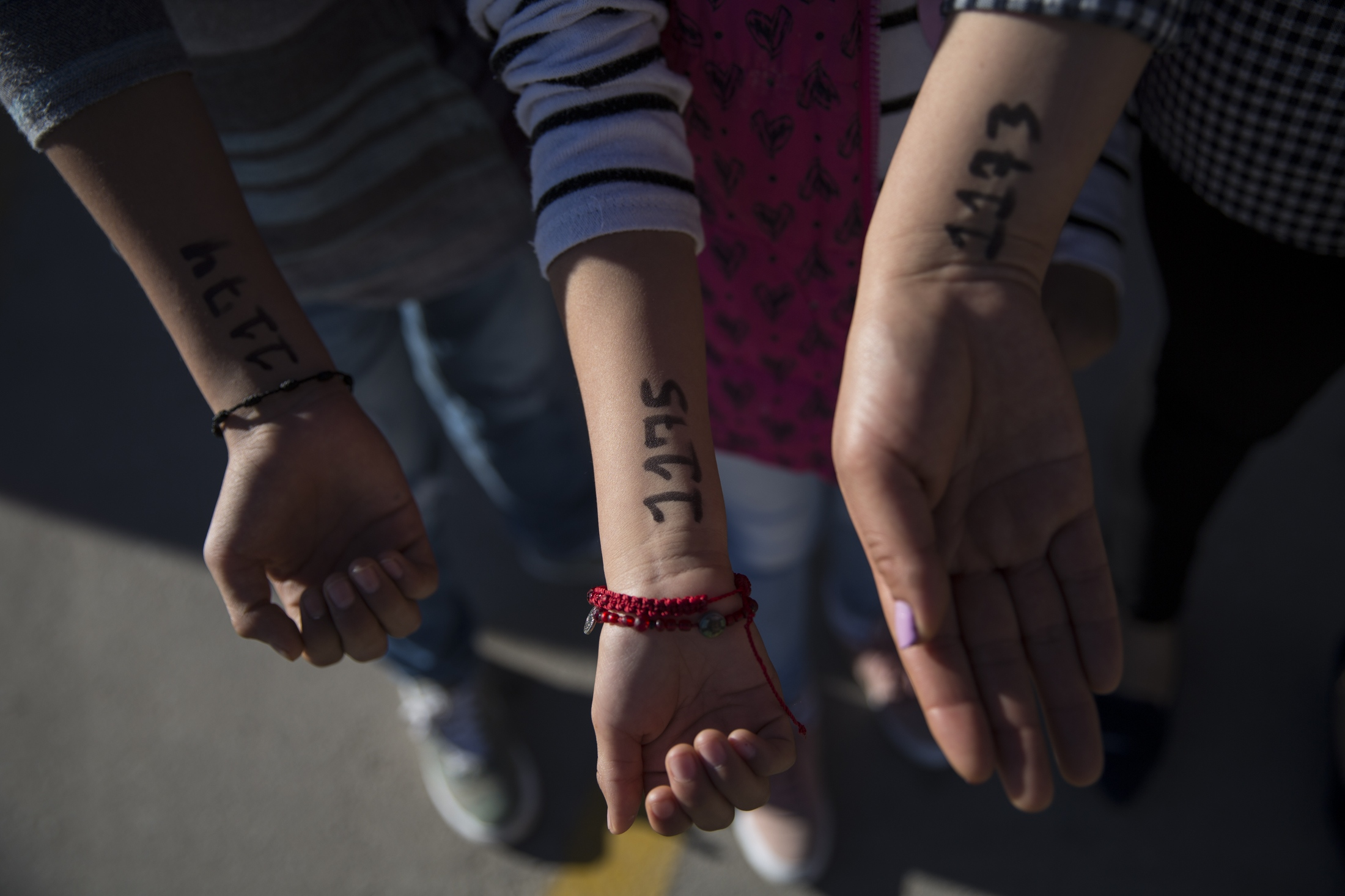 "A Mexican mother and her two children hold out their arms to show the numbers they were given to be on a list at Casa Del Migrante in Juárez, Mexico to seek political asylum in the United States on November 28, 2018. The shelter can house 280 people at a time. It was full on Wednesday when Lorena arrived. Her and her children were assigned the numbers 1173, 1174 and 1175 and written on the inside of their wrists. The list was nearing 1,100. Lorena's  brother, who owned a business and refused to pay ""quotas"" to the cartels, was killed. Immediately after, the man responsible for his killing began threatening her and her children."