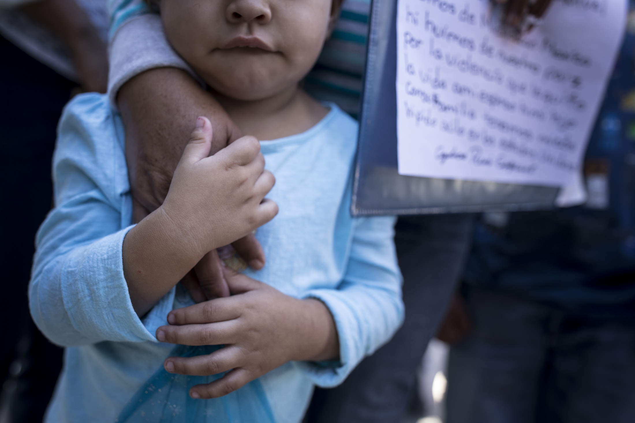 Three year old Ruth Sofia holds her grandmother's hand as they wait at the international boundary line on the Paso Del Norte International Bridge between Juárez and El Paso as they seek asylum in the United States on June 18, 2018.