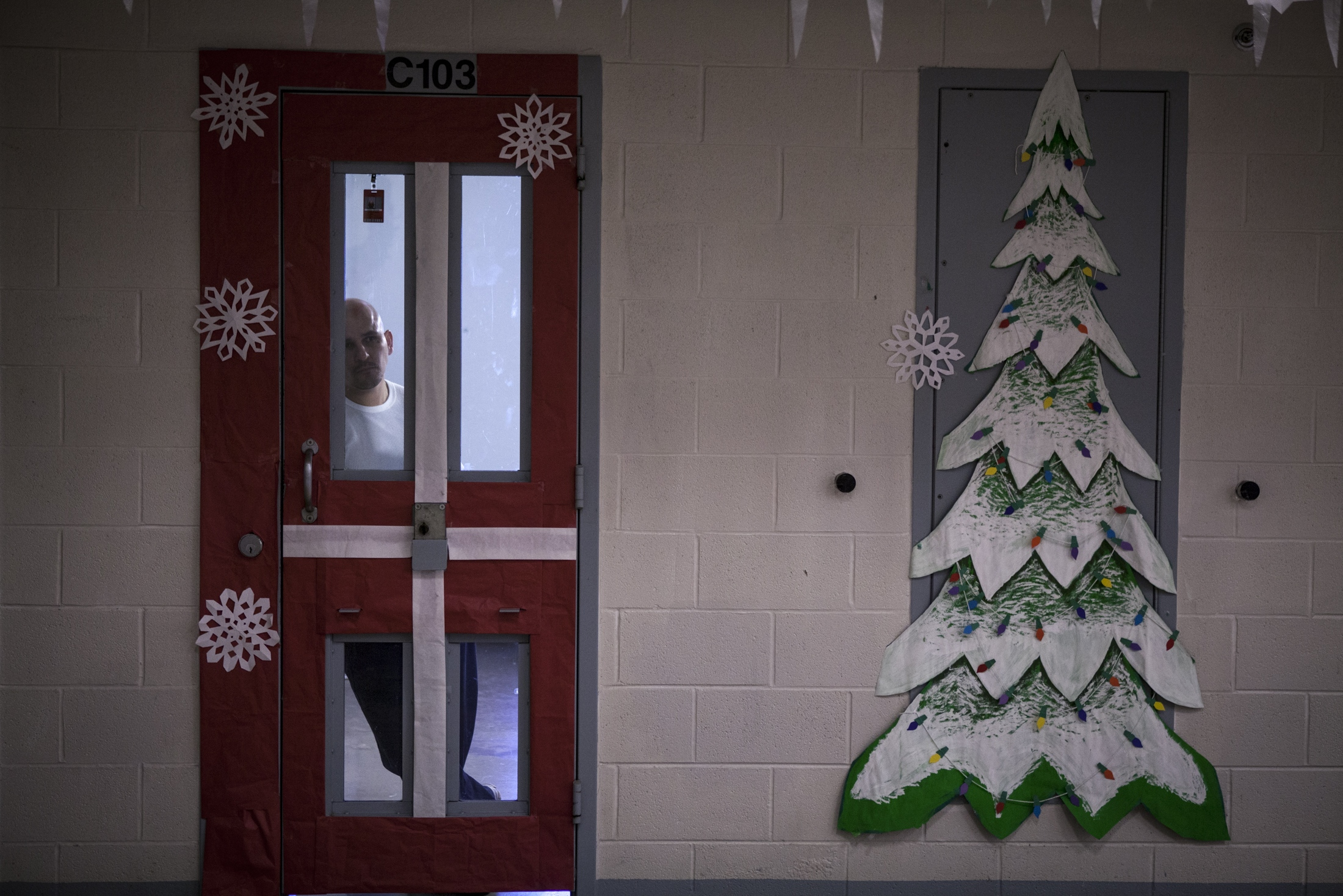 An inmate stares out of his cell while on lockdown as judges evaluate the inmates' pod decorations for an annual Christmas decorating contest at the Guadalupe County Corrections Facility.