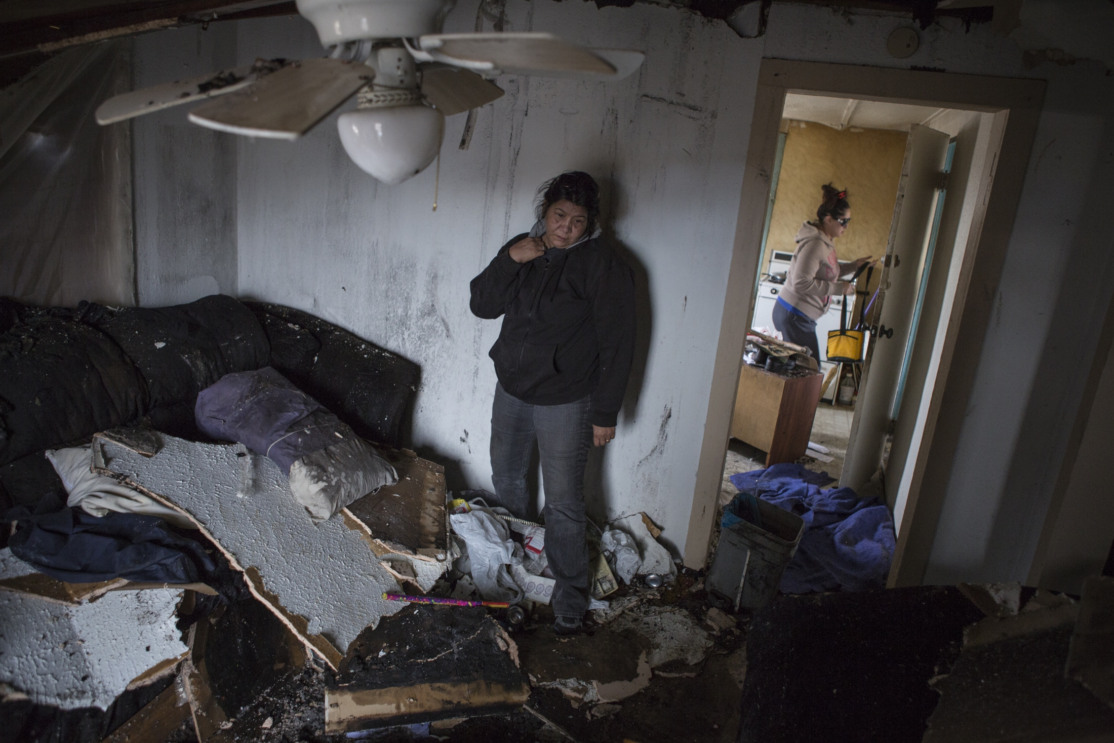 Debra Trujillo stares at the destruction to her ex-husband's home where emergency responders found Gene Garcia asleep on his couch while the home was still in flames. A chimney fire spread to the roof and neighboring rooms causing the roof to collapse moments before he was rescued.