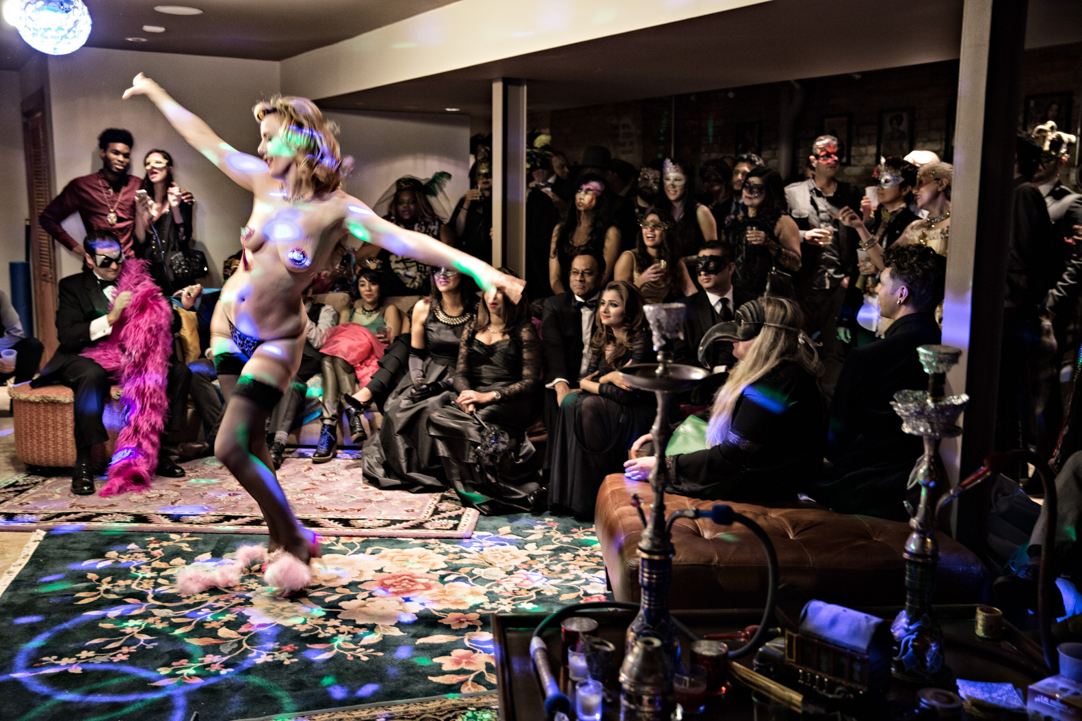 Red Hot Annie performs her act in front of an audience at a private residence during a New Year's Eve party. In addition to regular stage performances, Vaudezilla members are often booked for private celebrations.