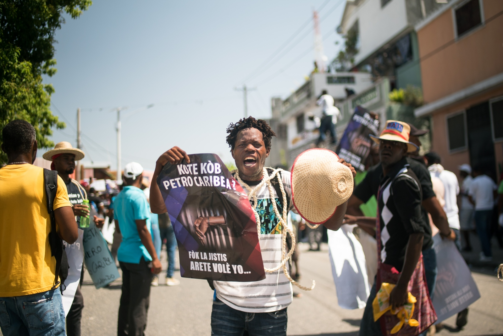 """Photography image - A protestor holds a banner and rope demanding for accountability and an end to corruption during the protest. Protesters gathered to demonstrate against the $3.8 billion that the government and private sector has been accused of embezzling from Venezuela's subsidized PetroCaribe oil program. The revenue was supposed to go toward financing economic and social programs. The PetroCaribe Challenge was started after Haitian filmmaker Gilbert Mirambeau Jr. posted on social media asking: """"Kot Kòb PetroCaribe a,"""" or """"Where did the PetroCaribe money go?"""" With a large youth, grassroots base, ongoing demonstrations across Haiti asking for accountability and denouncing corruption. Haiti, 2018."""