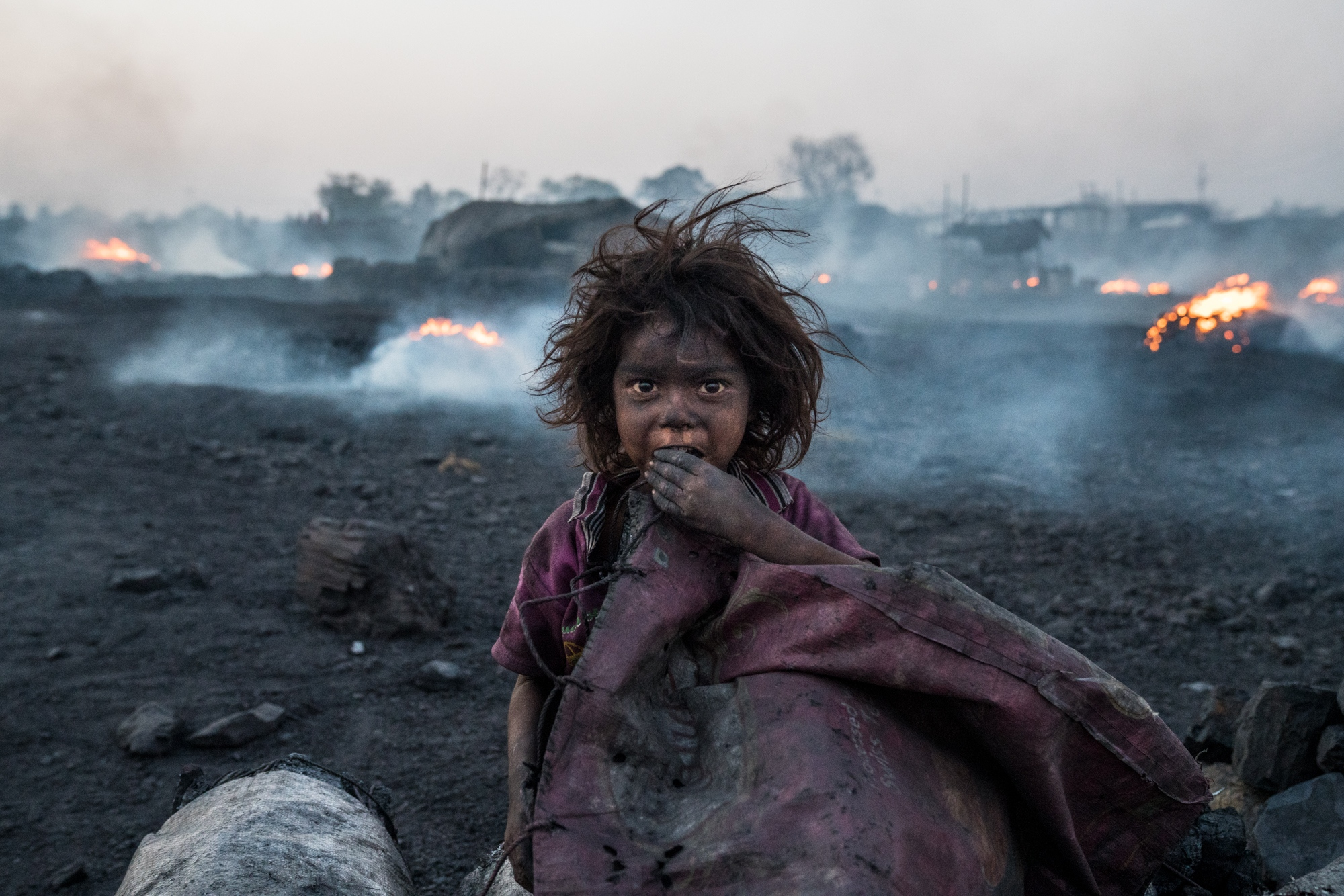 A child, covered in coal dust and breathing in deadly black carbon particles and gases, sits inside a black-market charcoal producing area nearby one of India's largest coal mining areas in the state of Jharkhand.